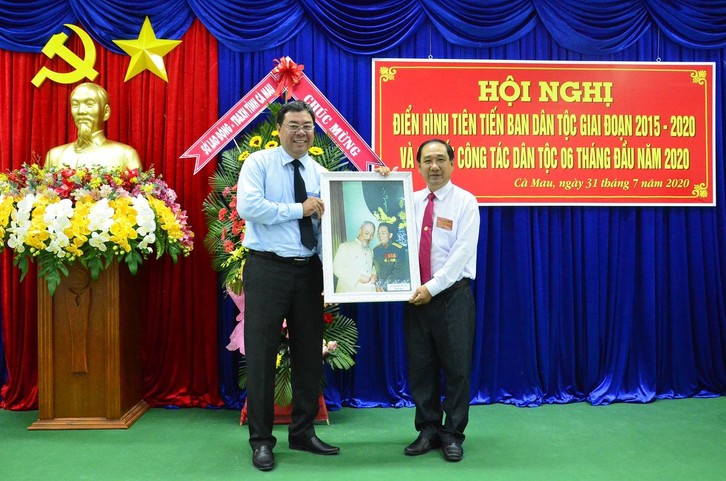 Ông Tào Việt Thắng, Phó Vụ trưởng Vụ Địa phương III (bên trái) trao quà và chúc mừng Ban Dân tộc tỉnh Cà Mau