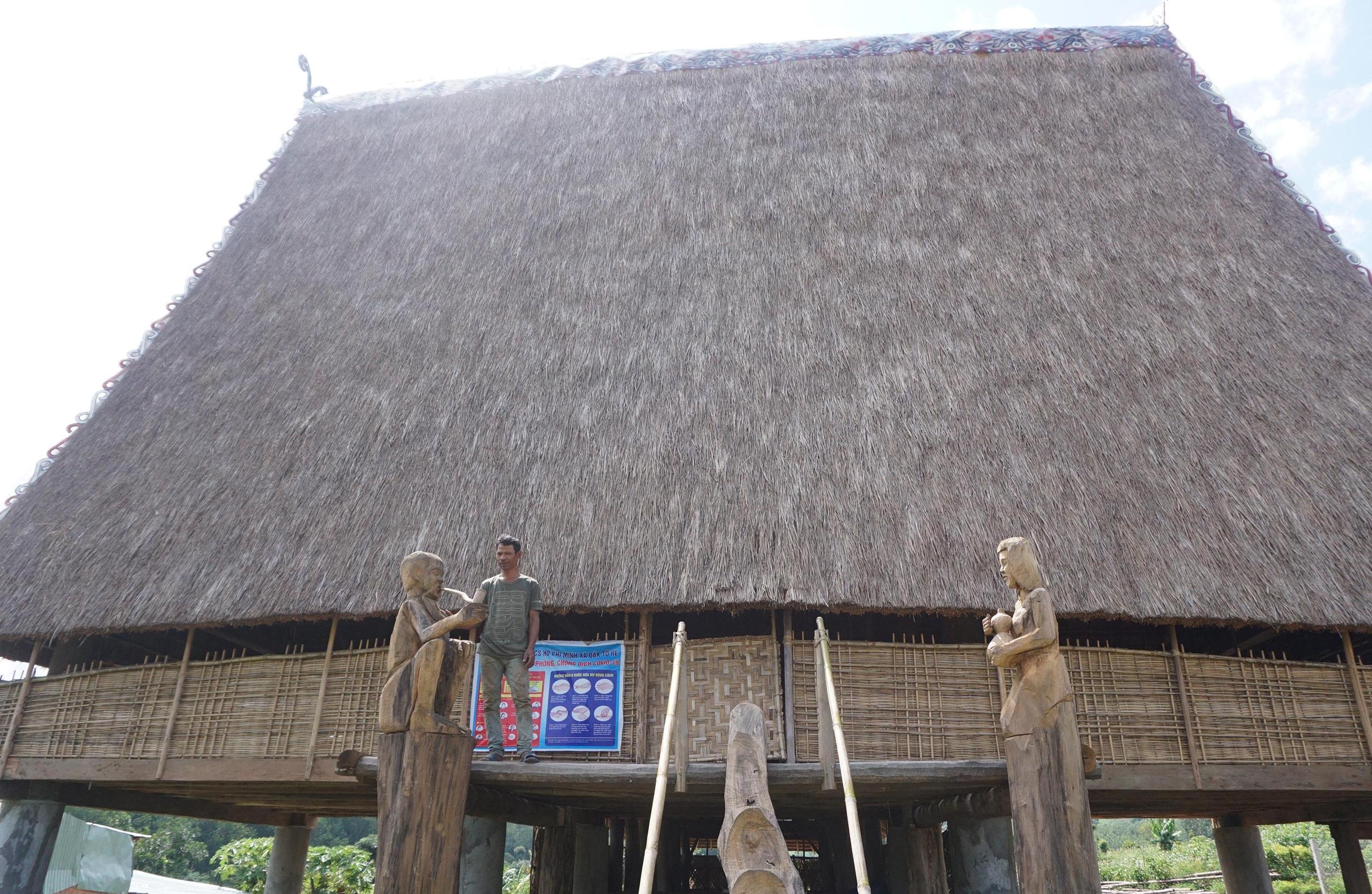 Ông A Tân giới thiệu bức tượng do chính tay ông làm đặt tại nhà rông của làng. Ảnh: T-T