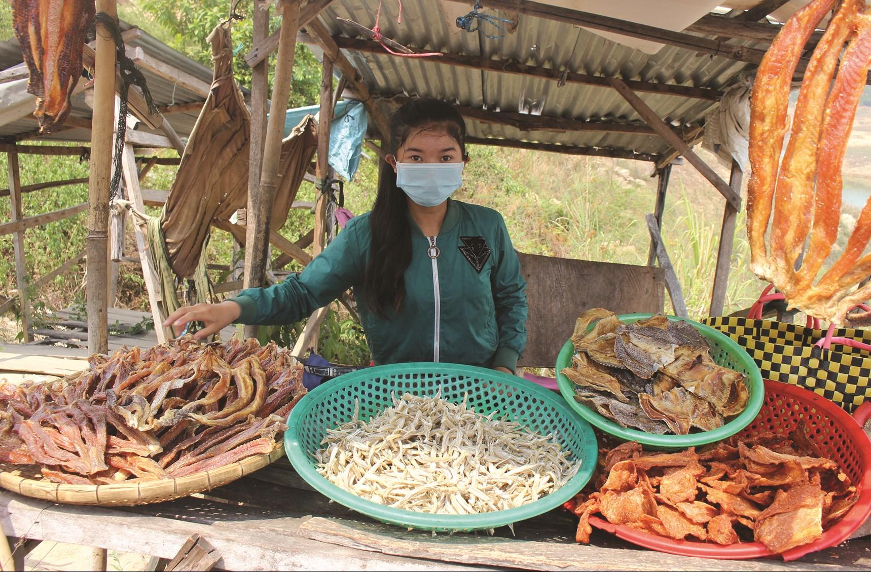 Trẻ em làng chài phụ gia đình bán khô cá trên chân cầu