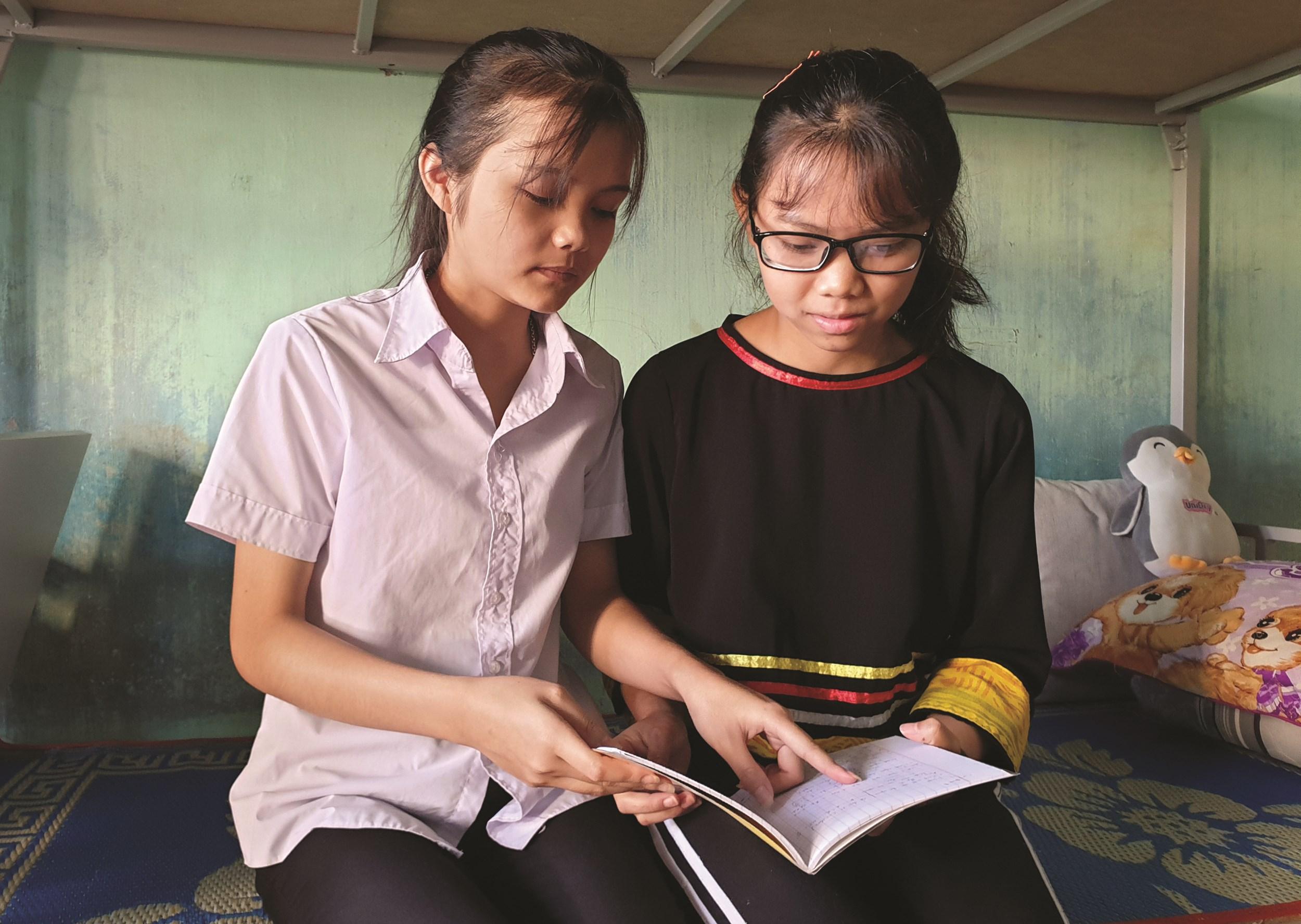 Ngoài giờ học trên lớp, Rơ Châm Ling (bên phải) cũng tranh thủ giúp đỡ bạn bè học tập