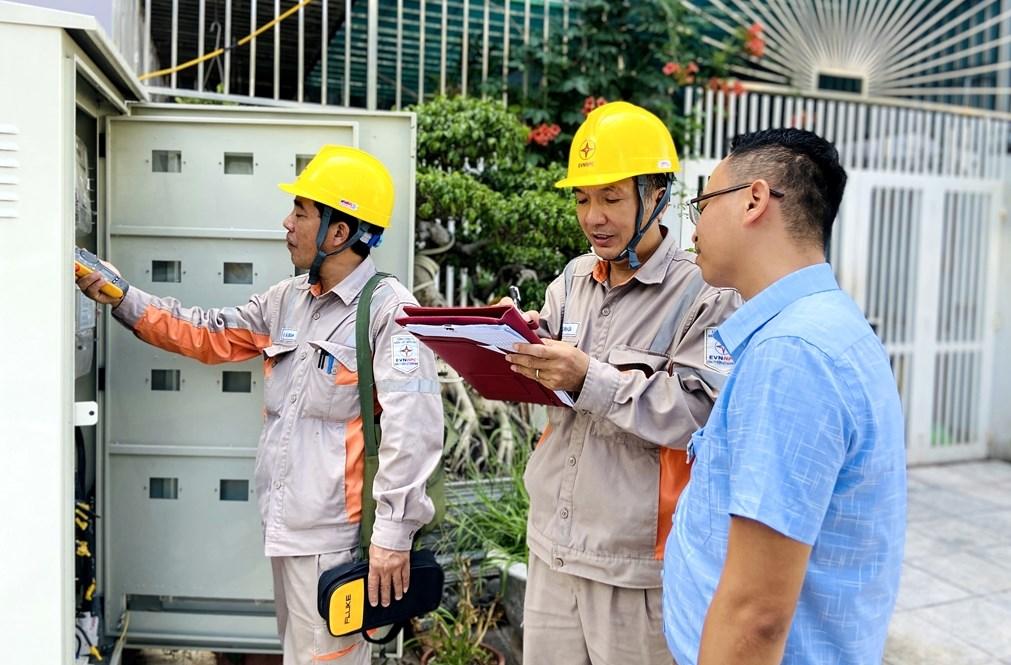 Cán bộ Điện lực kiểm tra công tơ của các gia đình có khiếu nại