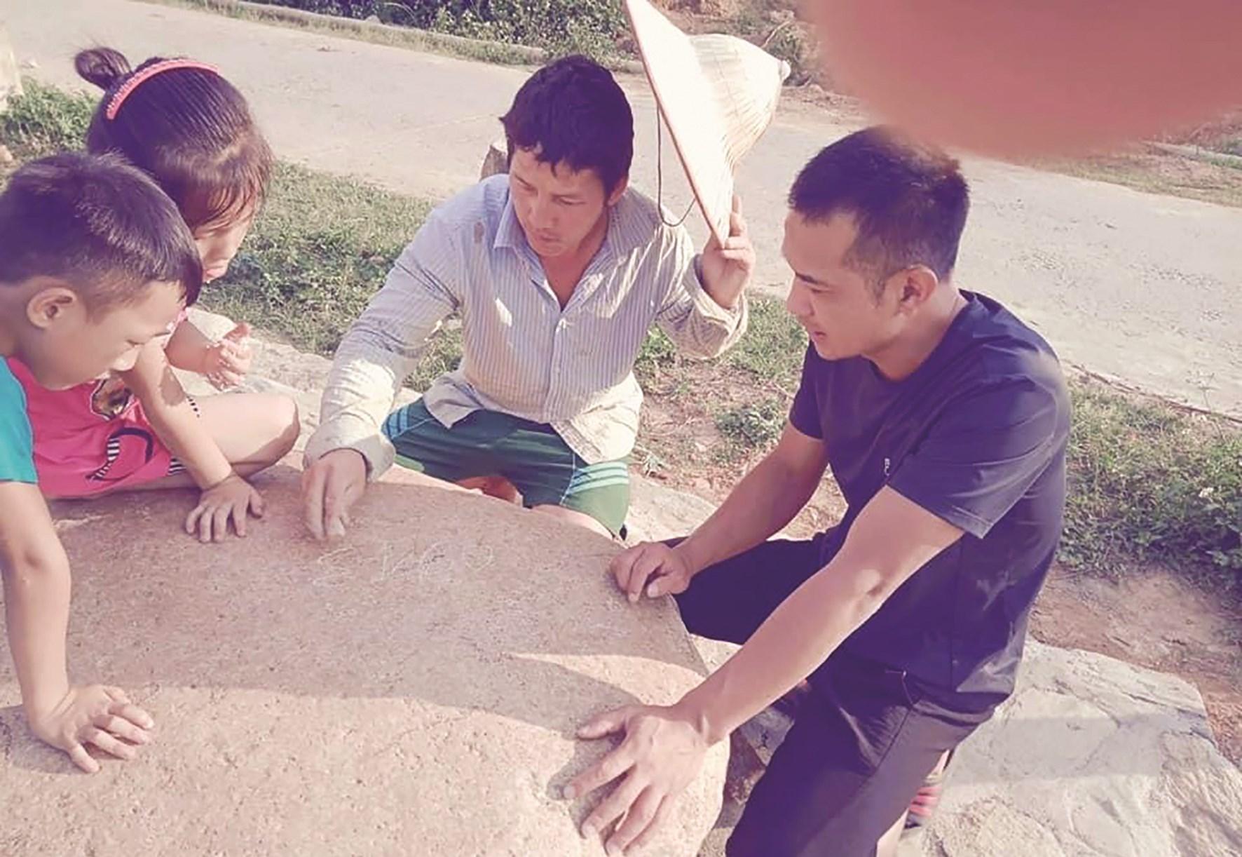 Anh Giàng A Phỏng (giữa) vẽ ý tưởng lên bàn đá để xây dựng điểm du lịch tại Bản Mù