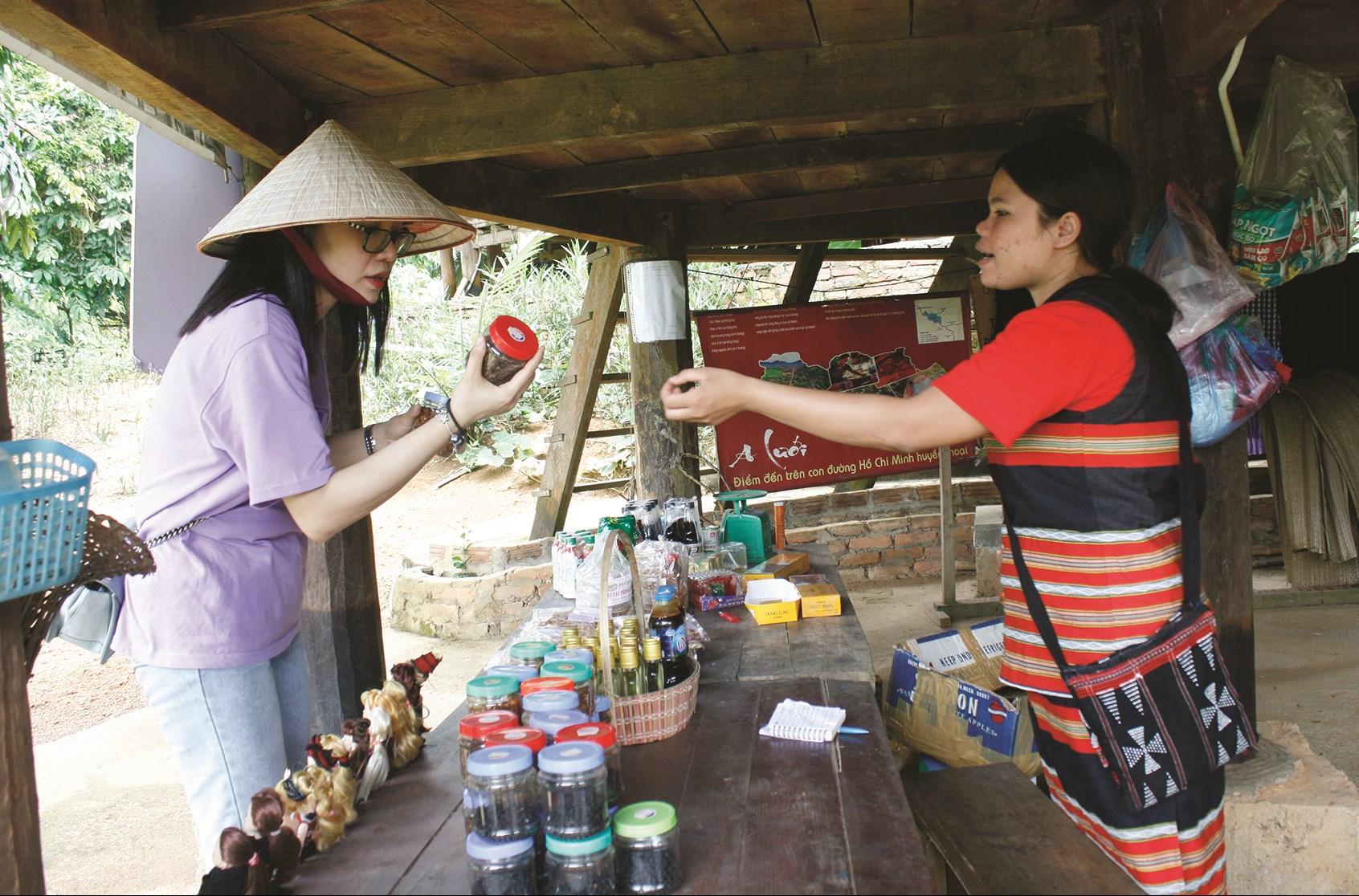 Chị Hồ Thị Nhôi (bên phai) giới thiệu sản phẩm, bán cho khách du lịch