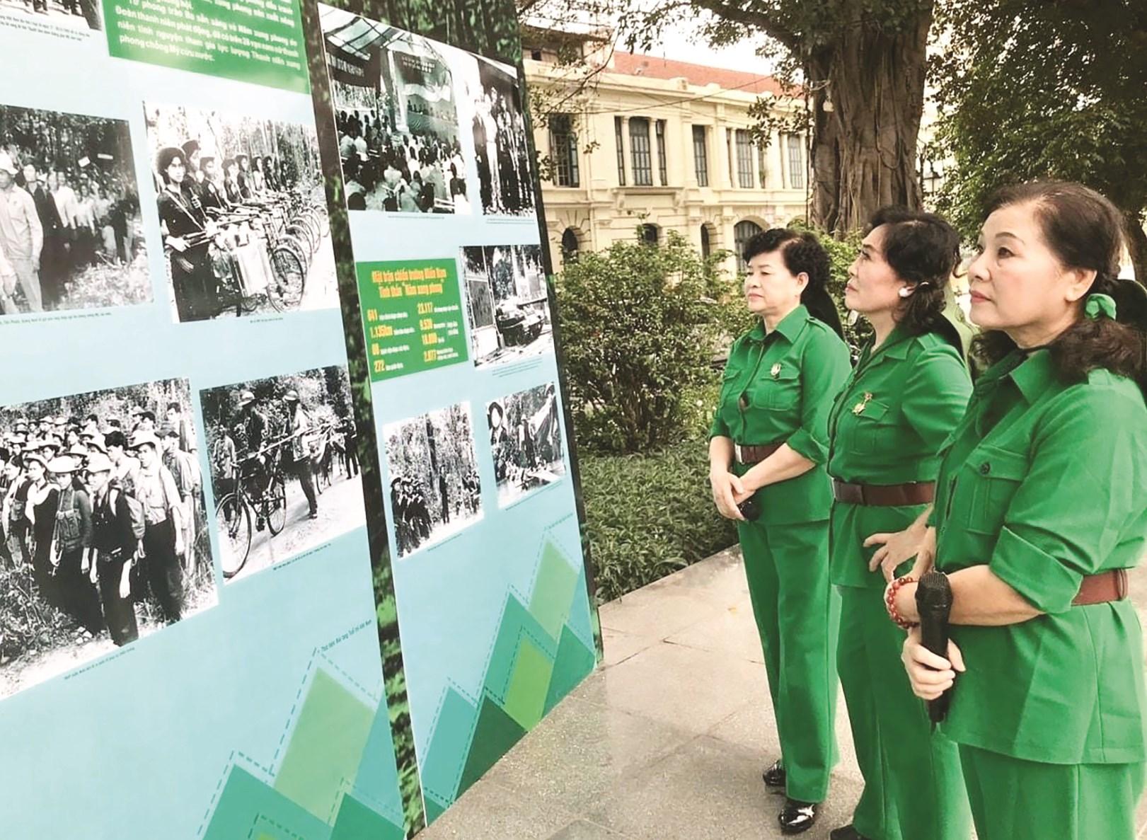 """Cựu TNXP bồi hồi xem lại những hình ảnh chiến trường năm xưa. (Ảnh chụp tại Triển lãm """"70 năm-sáng mãi tinh thần TNXP Việt Nam"""" tại Hà Nội, tháng 7/2020). Ảnh: Tư liệu"""