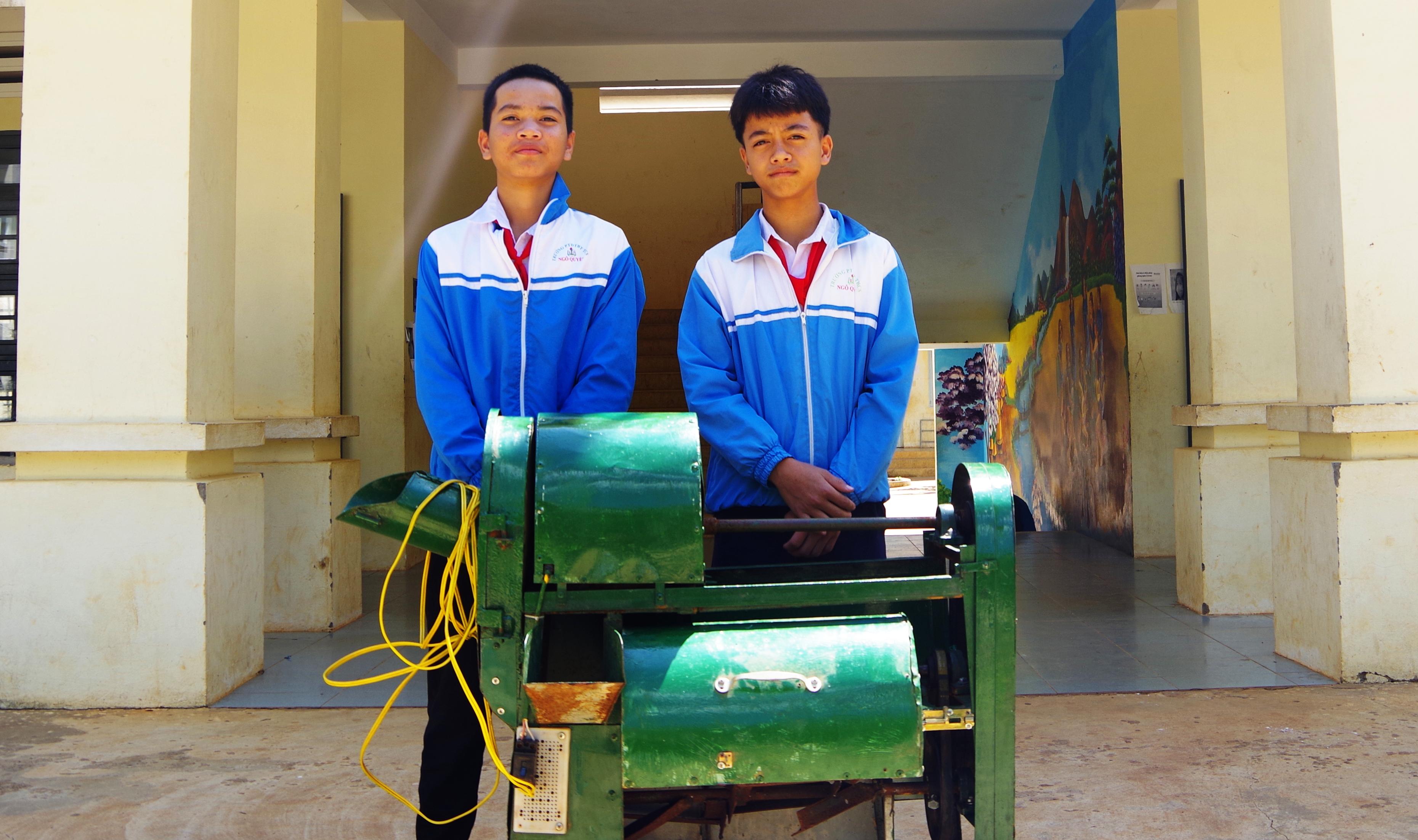 A Minh Khiêm (trái) và A Trường (phải) và chiếc máy cắt và trộn thức ăn trong chăn nuôi.