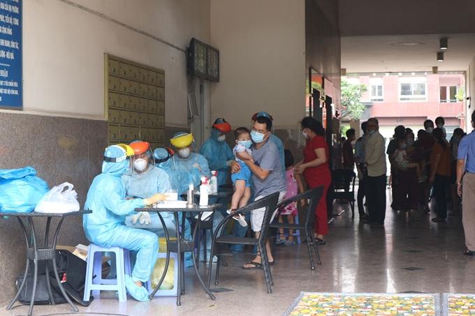 Nhân viên y tế lấy mẫu sàng lọc COVID-19 cho cư dân tại 1 chung cư ở TP.Hồ Chí Minh.