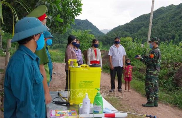 Lực lượng biên phòng tuyên truyền nâng cao nhận thức phòng chống dịch, phát khẩu trang miễn phí, sát khuẩn, kiểm tra y tế (đo thân nhiệt) cho người dân. Ảnh: Xuân Tiến-TTXVN