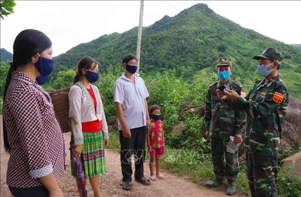 Chiến sĩ biên phòng thực hiện nhiệm vụ tại các chốt chặn hướng dẫn cách thức sử dụng, đeo khẩu trang đúng cách cho đồng bào dân tộc Mông trên khu vực biên giới. Ảnh: Xuân Tiến-TTXVN