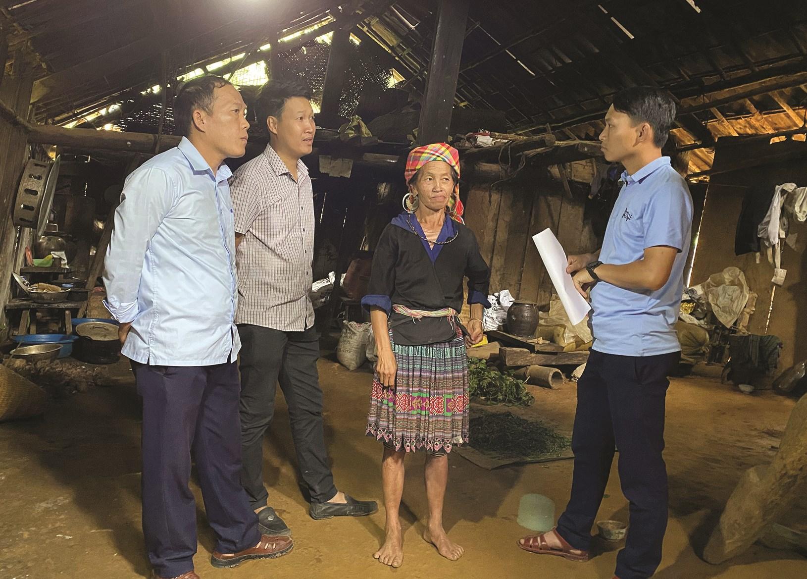Cán bộ huyện Mù Cang Chải và xã Mồ Dề đến thăm hỏi về đời sống của gia đình bà Mùa Thị Là, một trong những gia đình chưa được sử dụng điện lưới ở bản Háng Phừ Loa, xã Mồ Đề