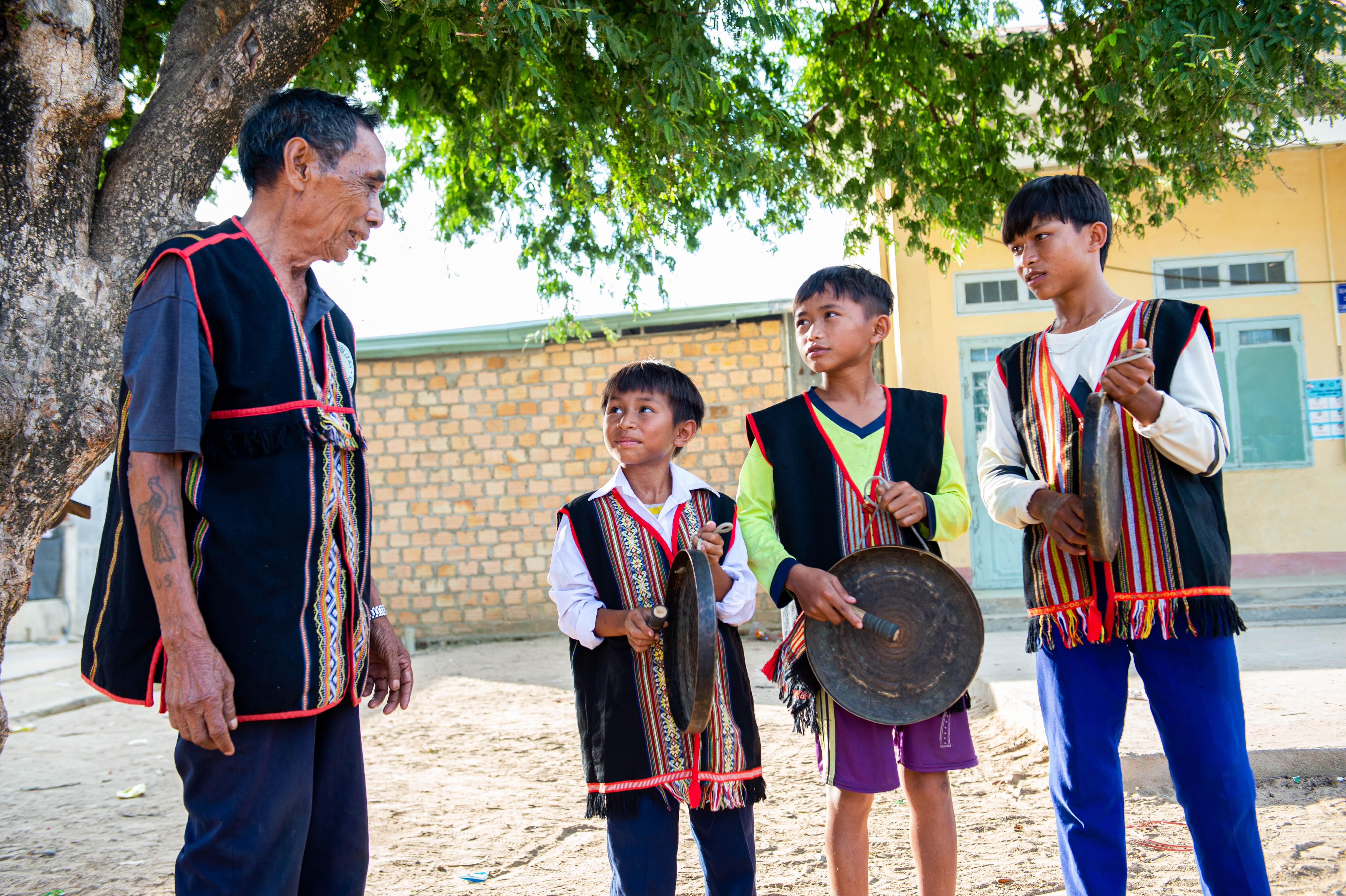 Nghệ nhân A Khiu truyền dạy cồng chiêng cho thế hệ trẻ trong làng. Ảnh: ĐT