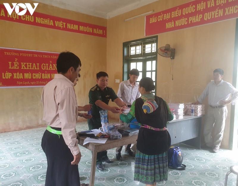 Thầy giáo quân hàm xanh ở Đồn biên phòng Nậm Lạnh (Sốp Cộp) phát sách vở, đồ dùng học tập cho học viên học lớp xóa mù chữ.