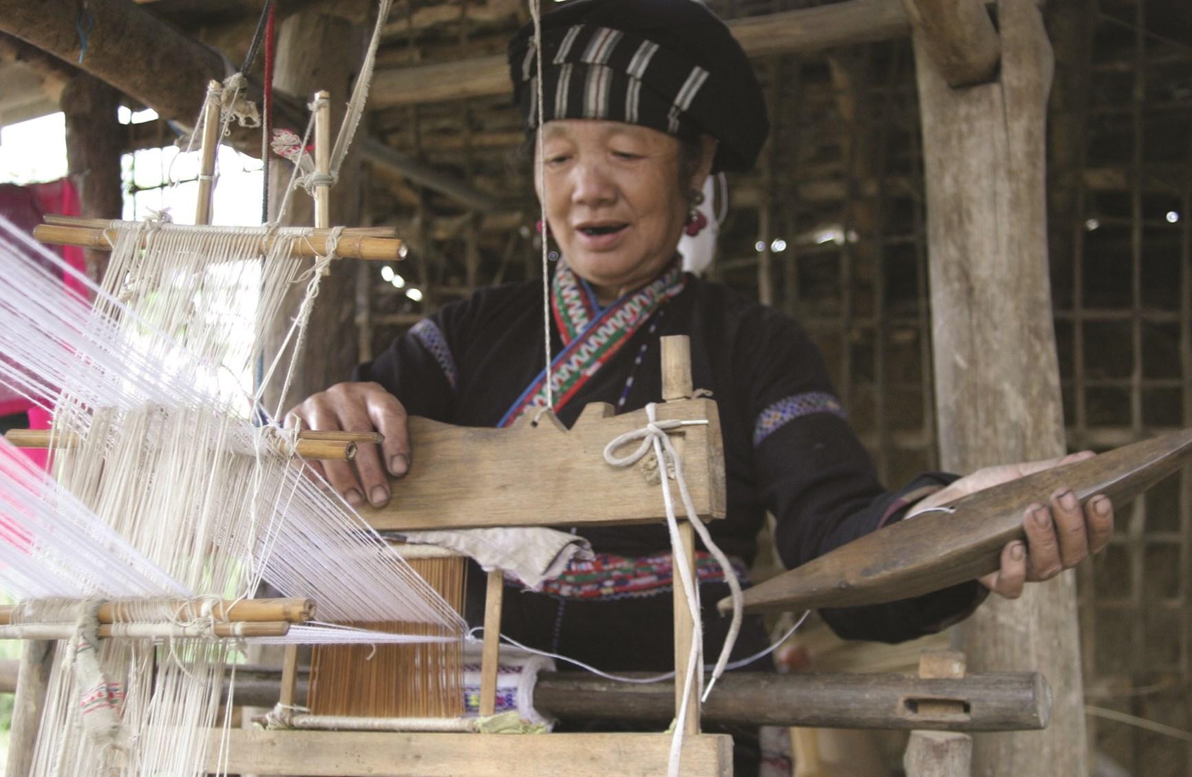Phụ nữ dân tộc Lự vẫn giữ nghề se tơ dệt vải và may váy áo truyền thống