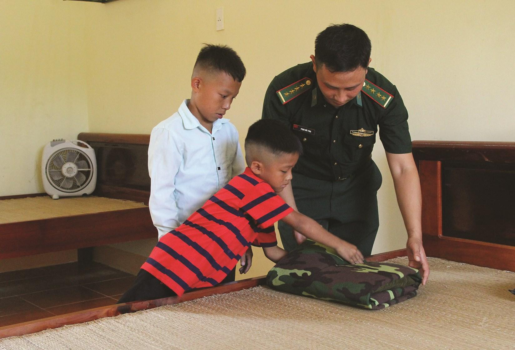 Đại úy Phạm Đức Tính hướng dẫn hai cháu (Khang và Linh) gấp chăn màn mùa hè