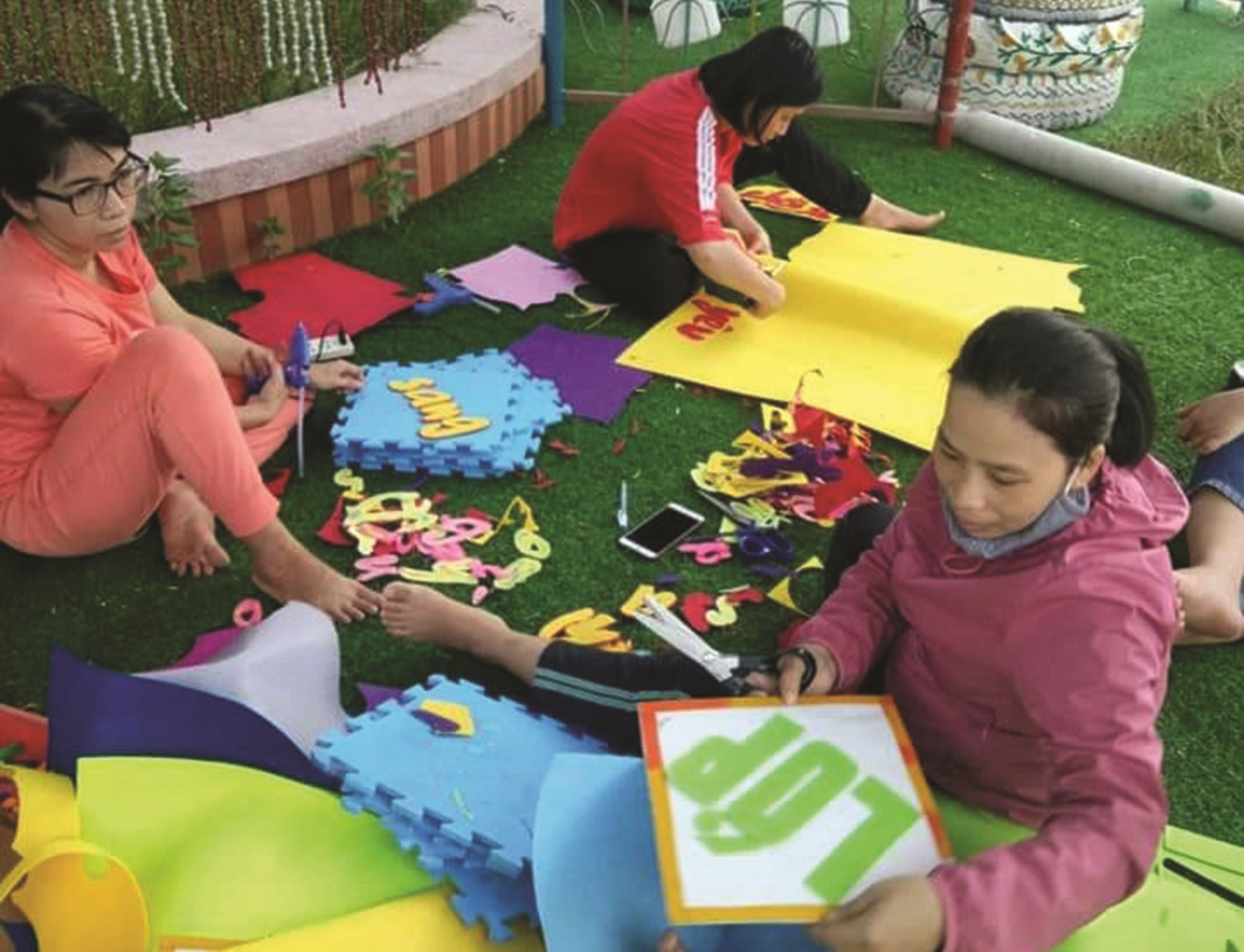 Các cô giáo Trường Mầm non Canh Vinh, huyện Vân Canh (Bình Định) đang cắt dán hình vẽ, con chữ để trang trí cho các góc chơi