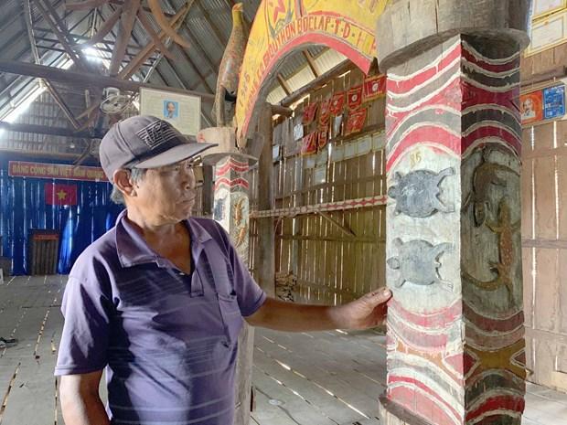 Già Drem trầm ngâm bên những bức khắc trong nhà rông từ xa xưa. Ảnh: baogialai.com.vn