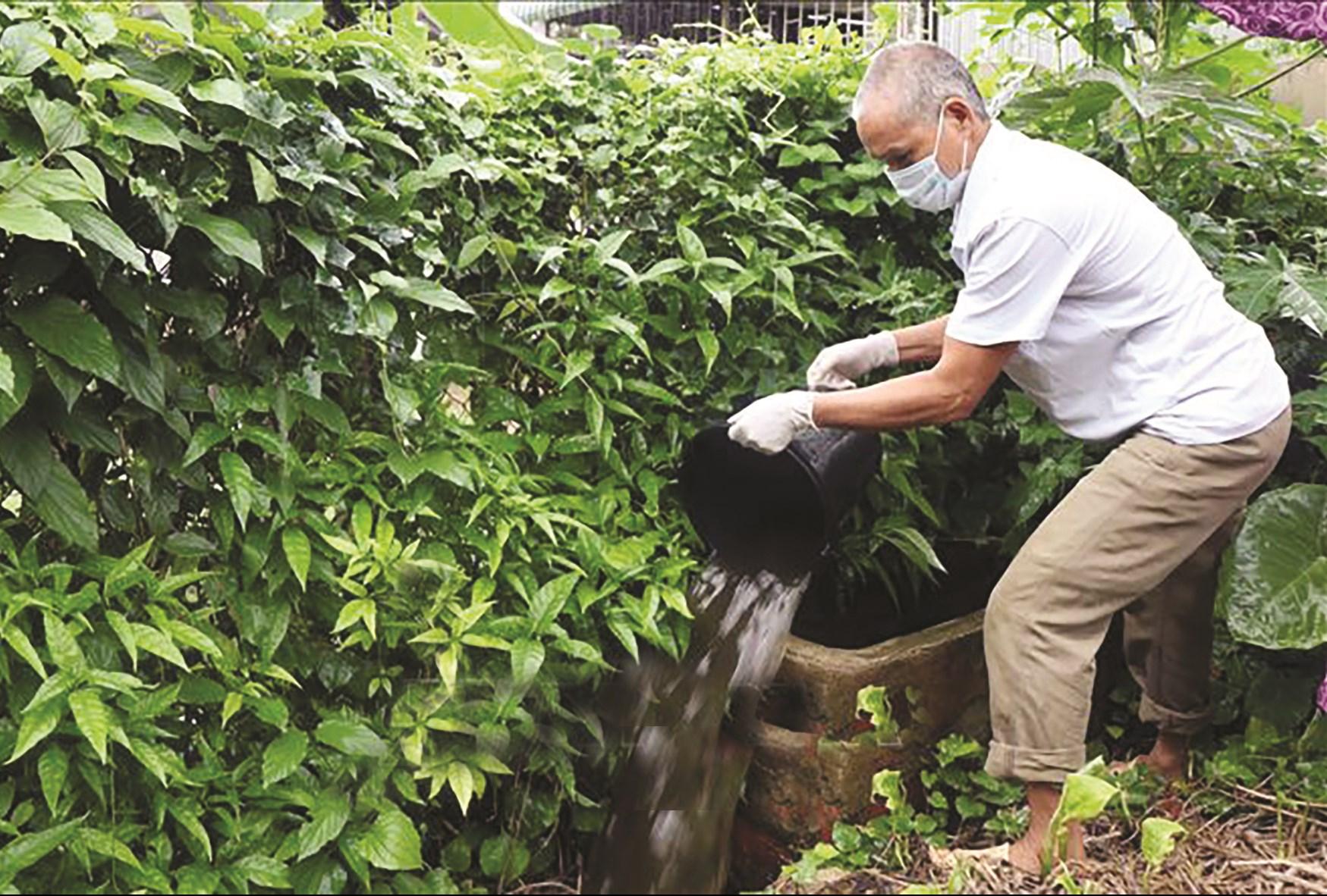 Người dân thị trấn Hát Lót thau rửa bể chứa nước mưa để diệt bọ gậy.
