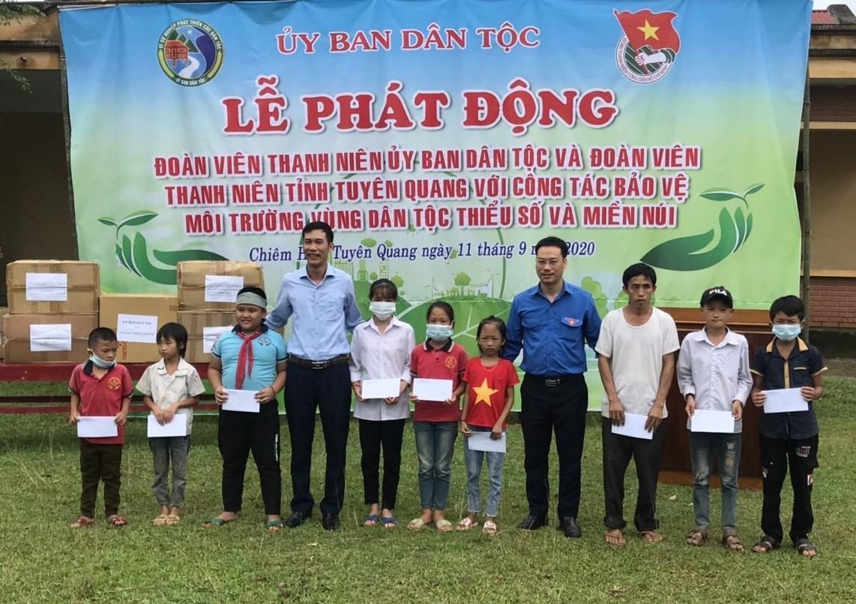 Ông Trần Văn Đoài, Phó vụ trưởng Vụ Tổng hợp và ông Nguyễn Văn Chính, Bí thư Đoàn thanh niên UBDT tặng quà của UBDT cho các học sinh có hoàn cảnh khó khăn