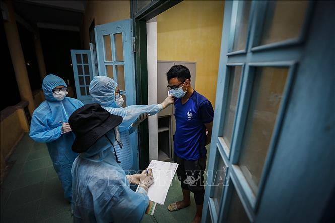 Theo dõi sức khoẻ người dân trong khu cách ly phòng dịch COVID-19. Ảnh: TTXVN