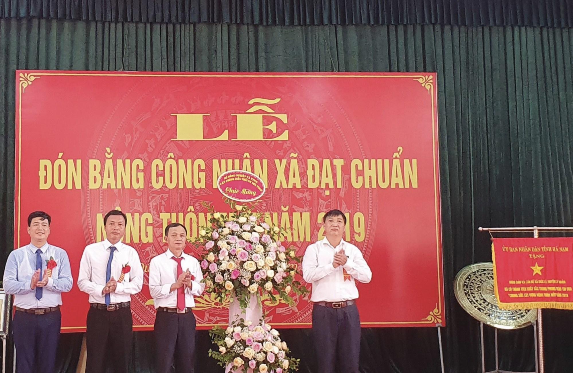 Lãnh đạo Đảng ủy, HĐND, UBND xã Đức Lý nhận danh hiệu Bằng công nhận NTM, Cờ Thi đua và hoa từ đại diện sở NN&PTNT tỉnh Hà Nam