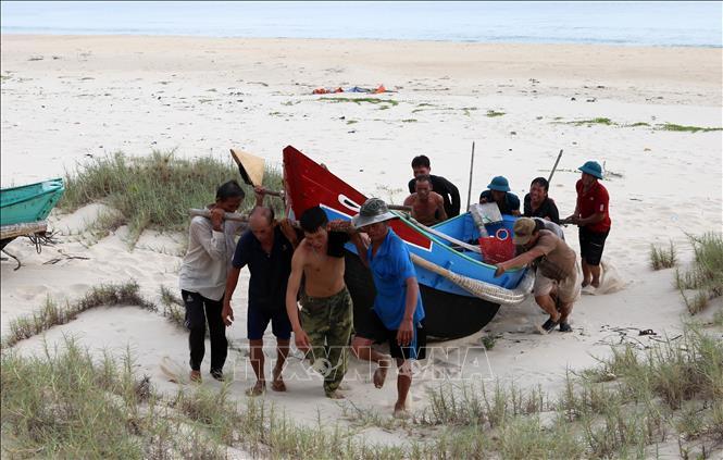 Ngư dân các xã bãi ngang của tỉnh Quảng Trị di chuyển thuyền lên cao để tránh trú bão số 5. Ảnh: Hồ Cầu/TTXVN