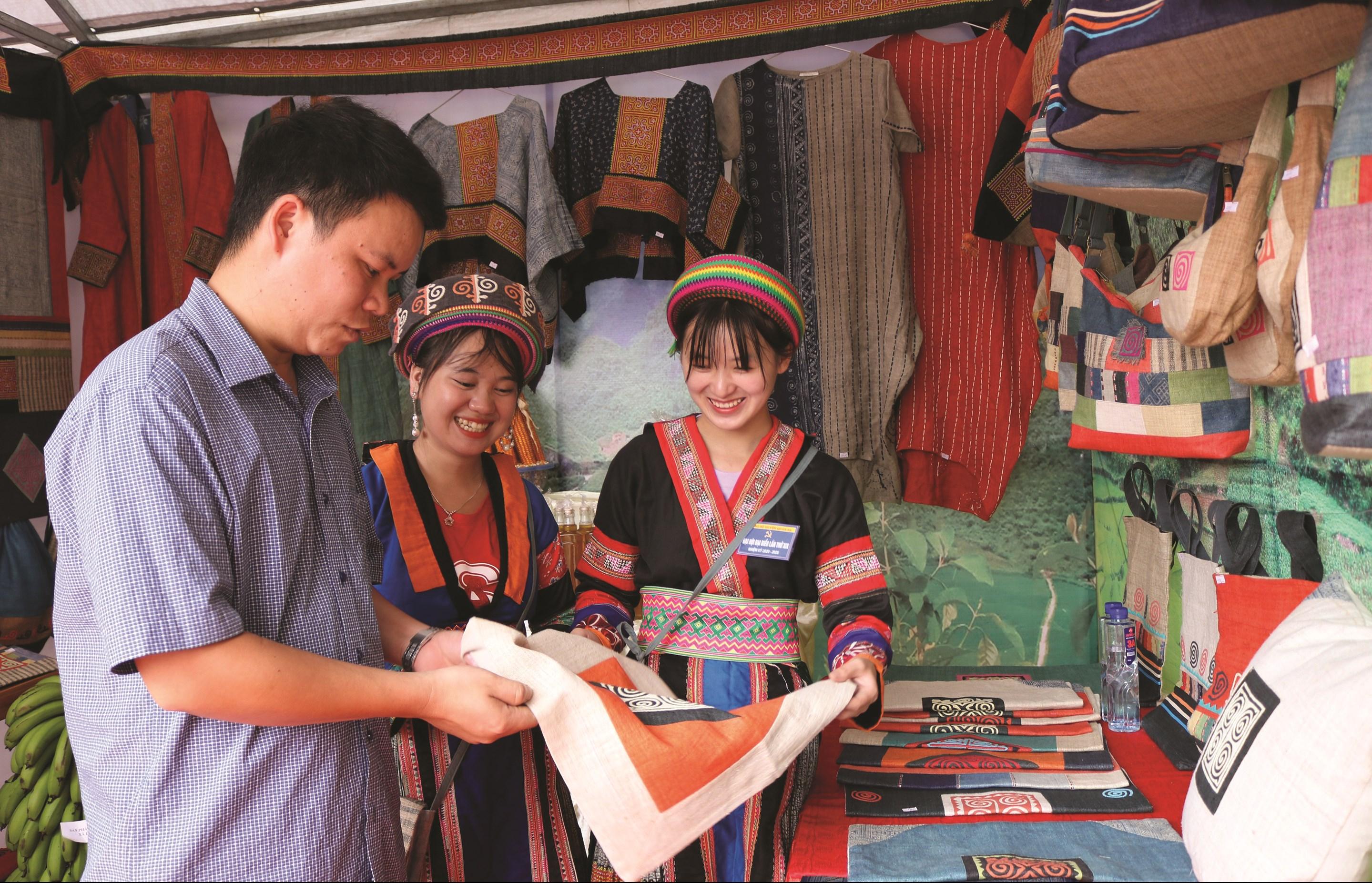 Các nhân viên Hợp tác xã dệt lanh Lùng Tám, mô hình phát triển du lịch hiệu quả ở huyện Quản Bạ đang giới thiệu sản phẩm lanh cho du khách.