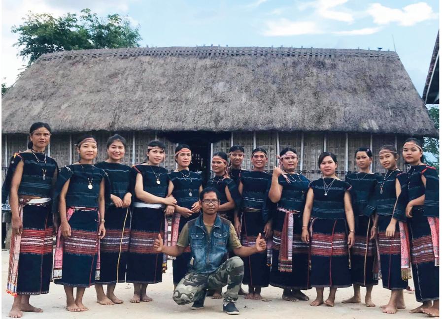 A Ngưi (ngồi giữa) và đồng bào dân tộc Ba Na tại buôn làng