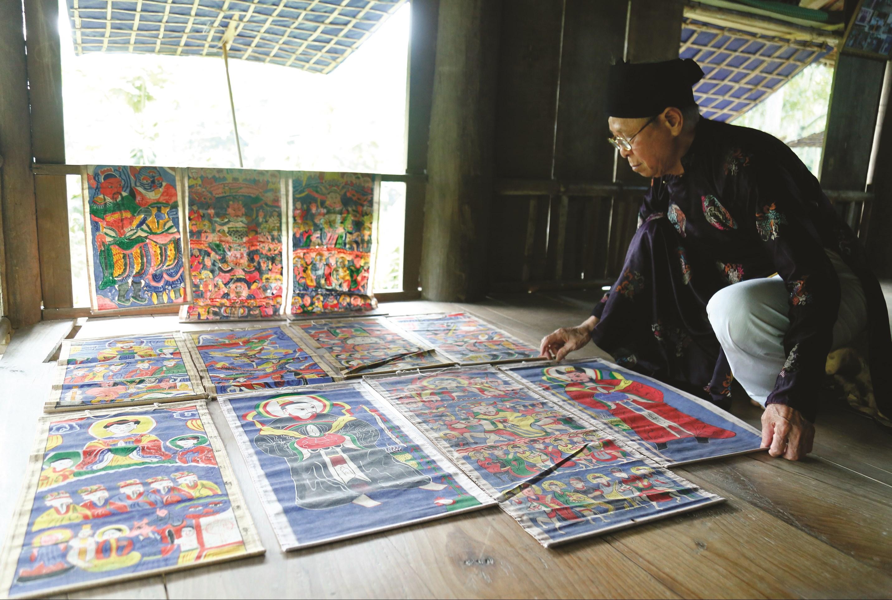 Nghệ nhân Dân gian Lê Hải Thanh phơi tranh thờ sau khi vẽ