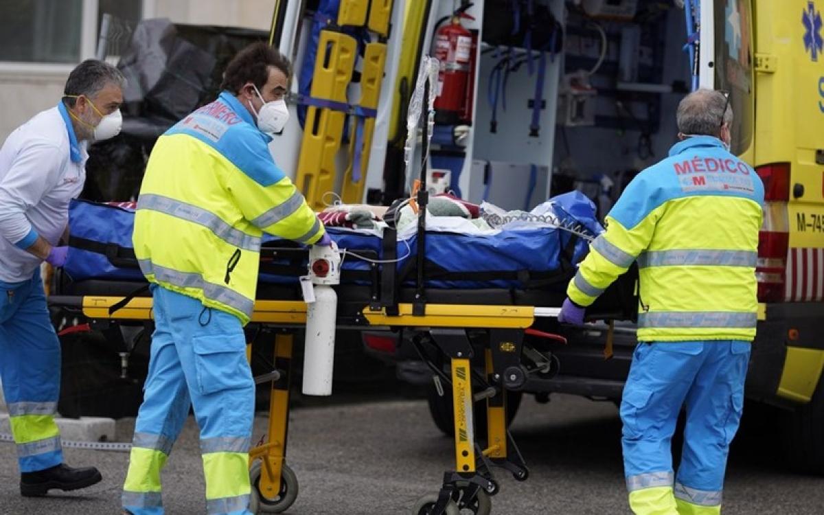 Đưa bệnh nhân Covid-19 tại Tây Ban Nha đi cấp cứu. Ảnh: Bloomberg.
