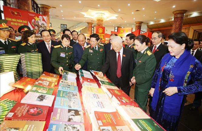 Tổng Bí thư, Chủ tịch nước, Bí thư Quân ủy Trung ương Nguyễn Phú Trọng và các đại biểu xem các ấn phẩm quốc phòng. Ảnh: Trí Dũng/TTXVN
