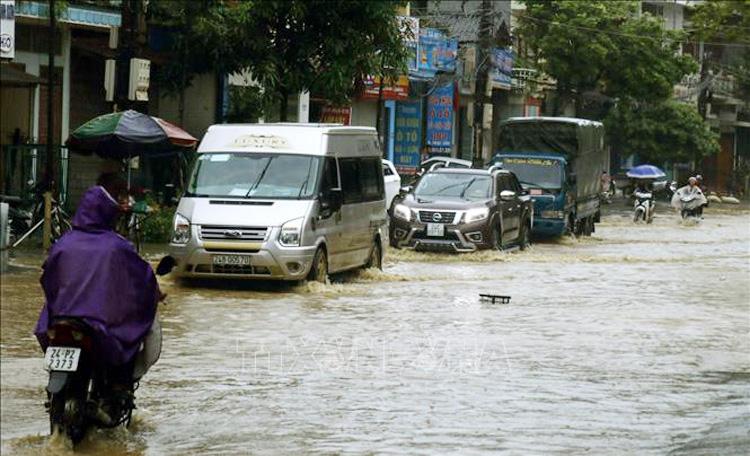 Ngập cục bộ trên đường Nhạc Sơn, thành phố Lào Cai, làm cho các phương tiện tham gia giao thông gặp nhiều khó khăn. Ảnh: Quốc Khánh - TTXVN