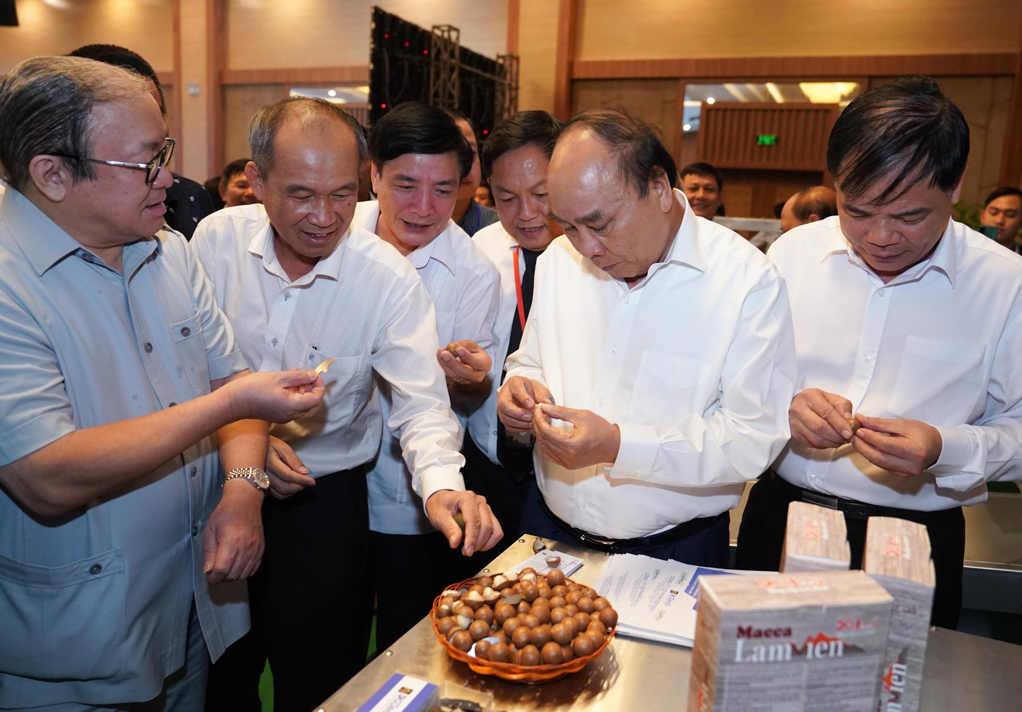 Thủ tướng Nguyễn Xuân Phúc thăm quan khu trưng bày các sản phẩm được chế biến từ hạt mắc ca. - Ảnh: VGP/Quang Hiếu