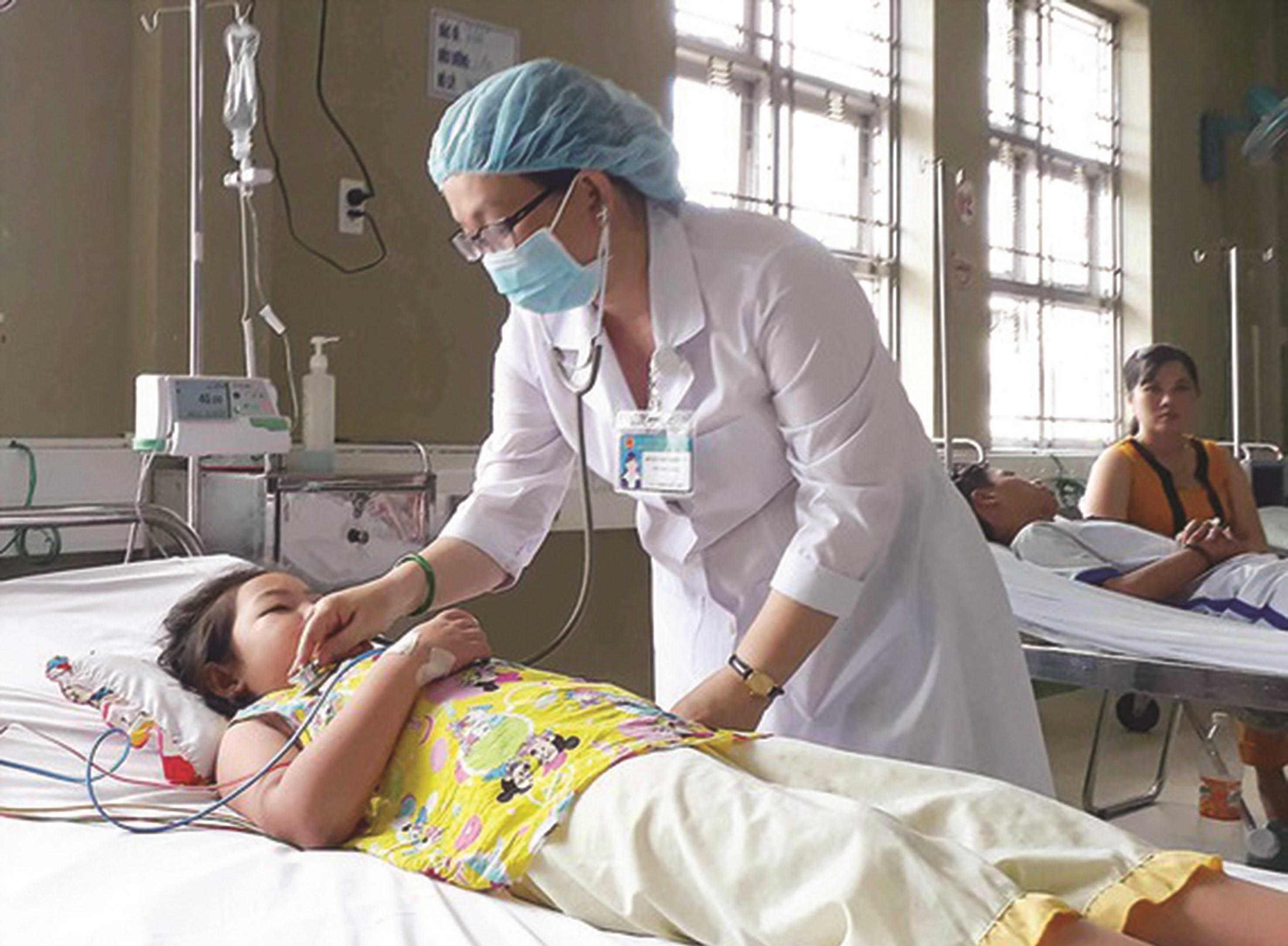 Bác sĩ kiểm tra thân nhiệt cho bệnh nhi bị sốt xuất huyết tại Bệnh viện Sản - nhi Cà Mau.
