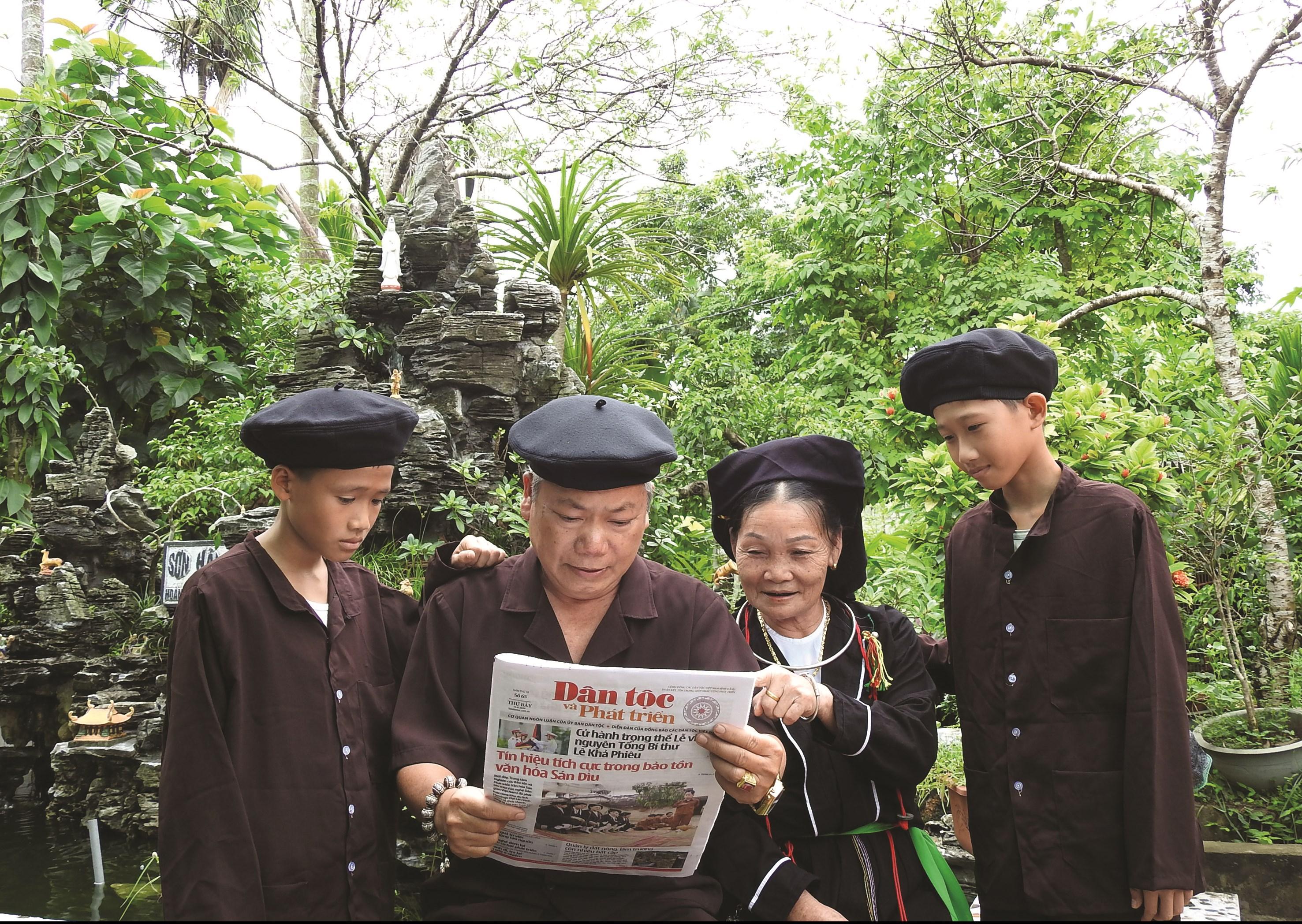 Ông Lục Văn Bảy chia sẻ thông tin trên Báo Dân tộc và Phát triển với các thành viên trong gia đình