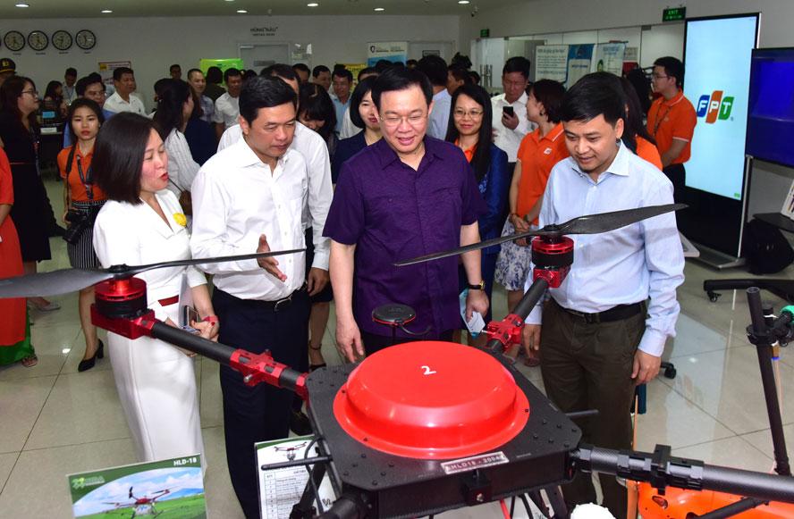 Bí thư Thành ủy Hà Nội Vương Đình Huệ tham quan các sản phẩm công nghệ cao tại Khu công nghệ cao Hòa Lạc. Ảnh: Viết Thành