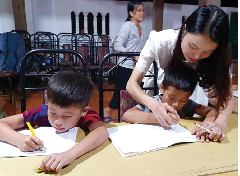 Cô giáo Triệu Thị Đào đang hướng dẫn các học trò viết chữ đẹp