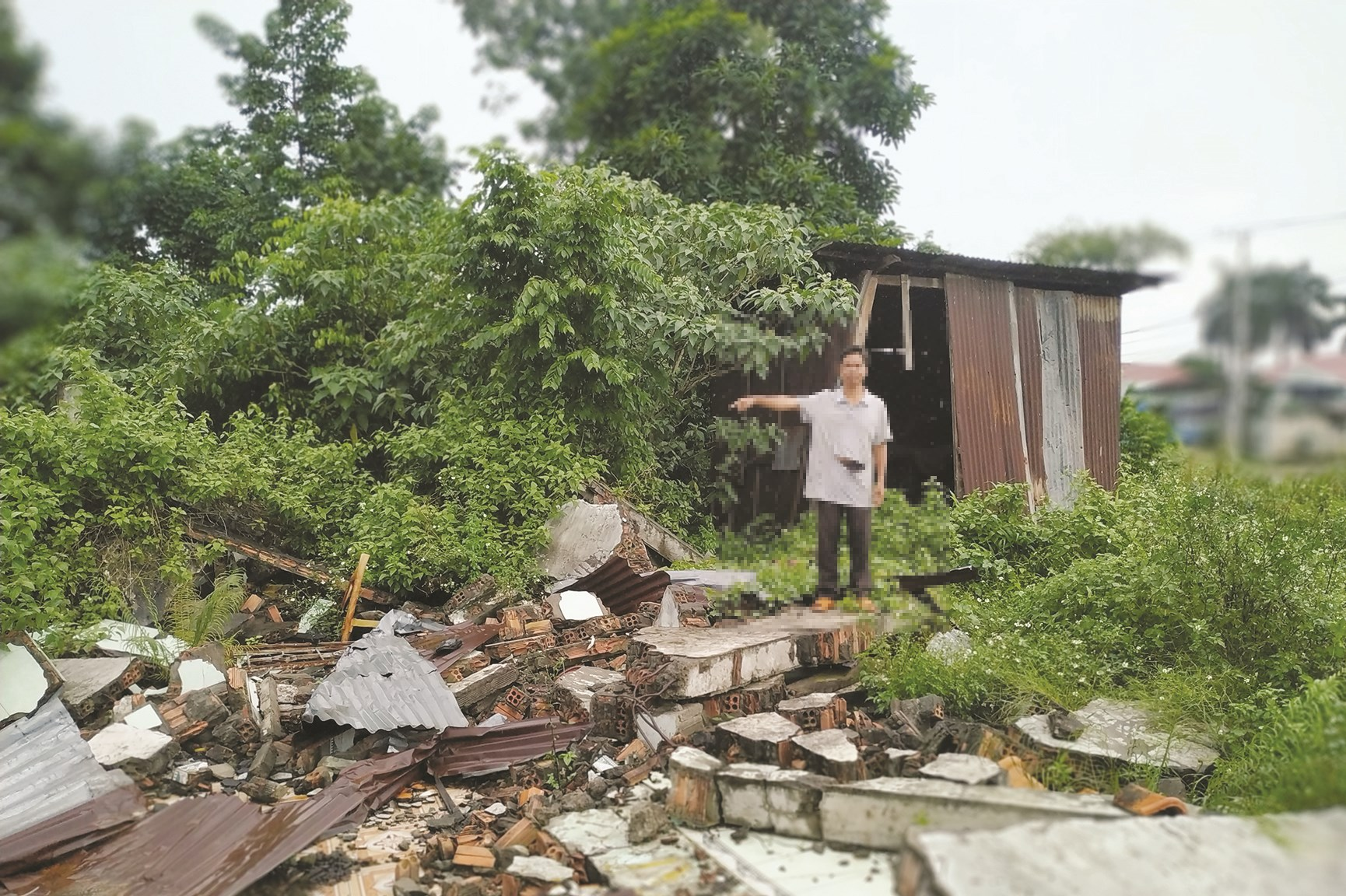 Ông Sú A Giểng bên đống đổ nát, nơi trước là ngôi nhà của gia đình nhưng đã bị nhóm người lạ cho xe ủi giật sập