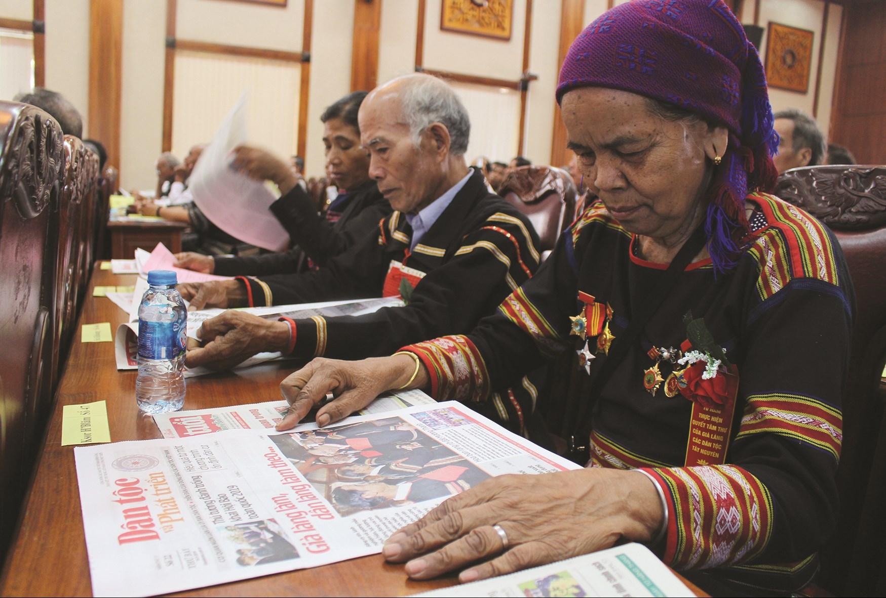 Già làng Ksơr H'lâm (bìa phải) là 1 trong 56 già làng tiêu biểu tỉnh Gia Lai thường xuyên đọc Báo Dân tộc và Phát triển.