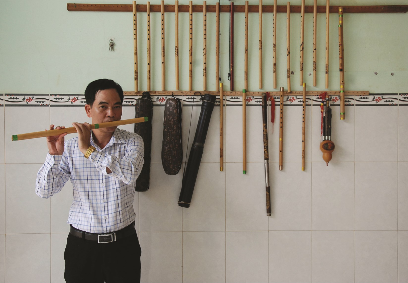 Anh Trần Hồng Cảnh với cây sáo dân tộc trưng bày trong gia đình anh