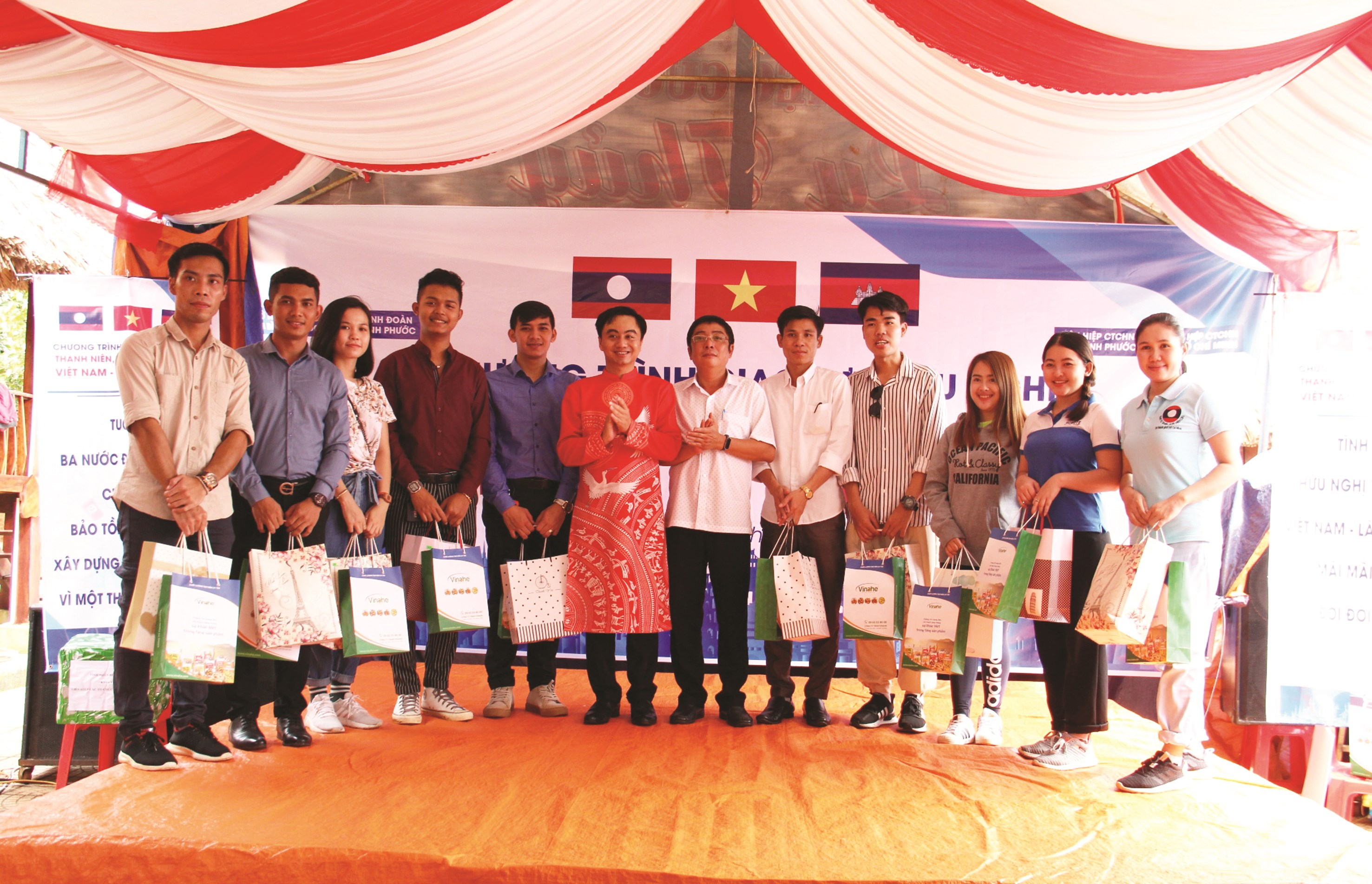 Bí thư Tỉnh Đoàn Trần Quốc Duy (mặc áo dài đỏ) và Phó Giám đốc Sở Ngoại vụ tỉnh Bình Phước Bùi Quốc Khánh (thứ sáu từ phải qua) tặng quà cho sinh viên Campuchia và Lào