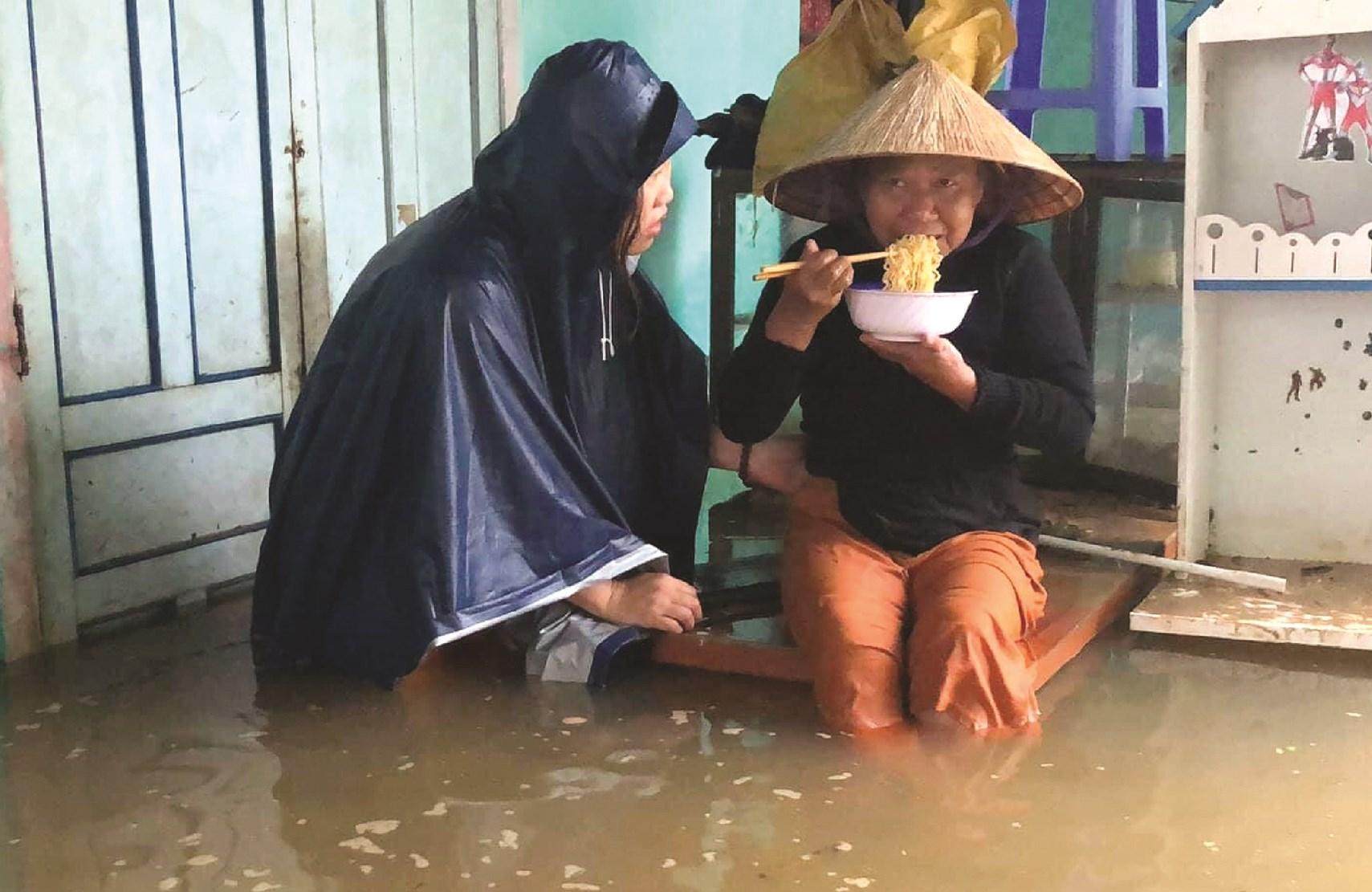 Hai người phụ nữ trong vùng lũ ở Quảng Trị, một người là người dân trong vùng lũ nhiều ngày thiếu lương thực đang bưng bát mỳ tôm, người còn lại là người mang lương thực đến cứu trợ