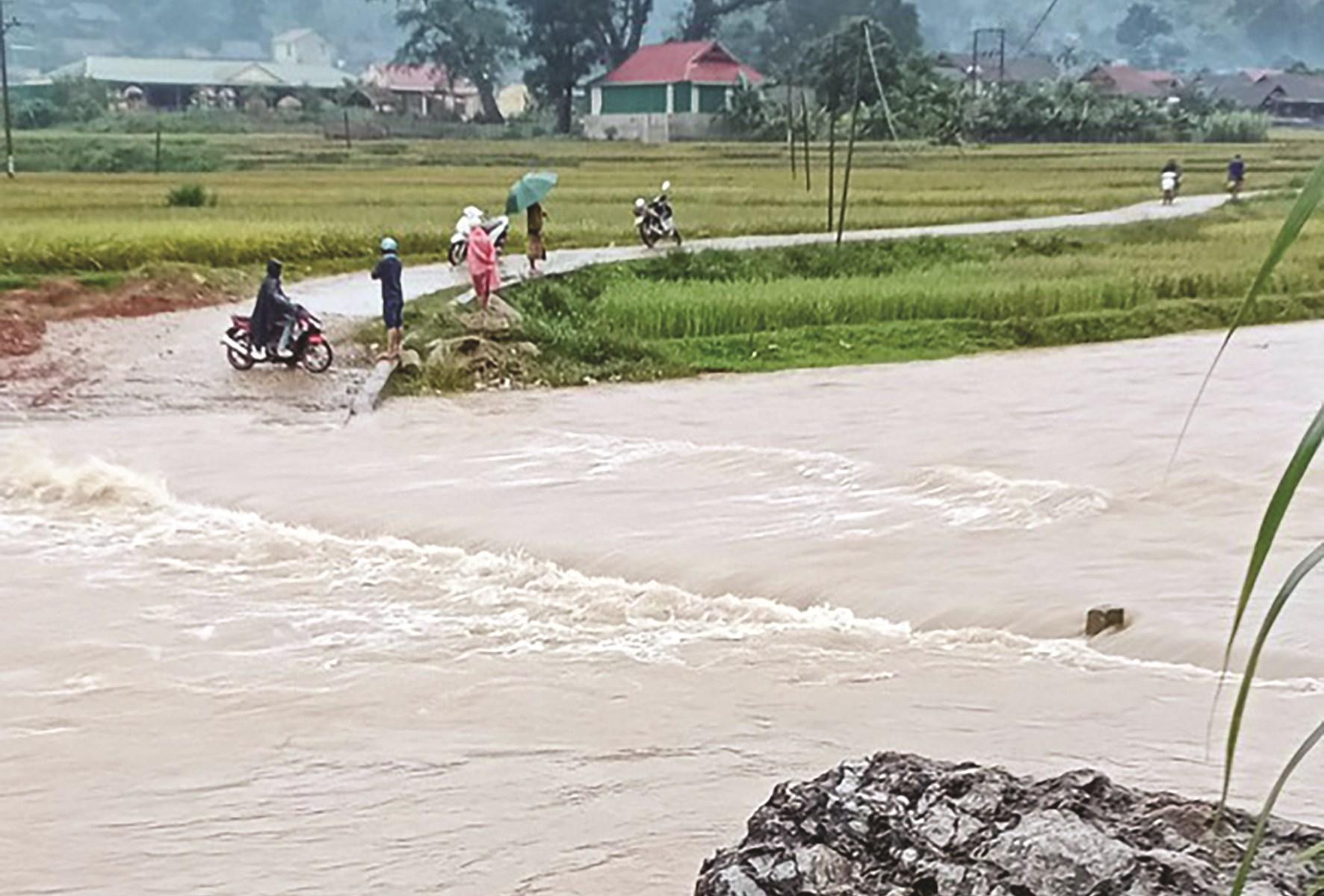 Nước tràn qua đường, dìm bản Cắm, xã Cắm Muộn, huyện Quế Phong ngập nước từ chiều 18/10, người dân không thể qua lại được. (Ảnh CTV)
