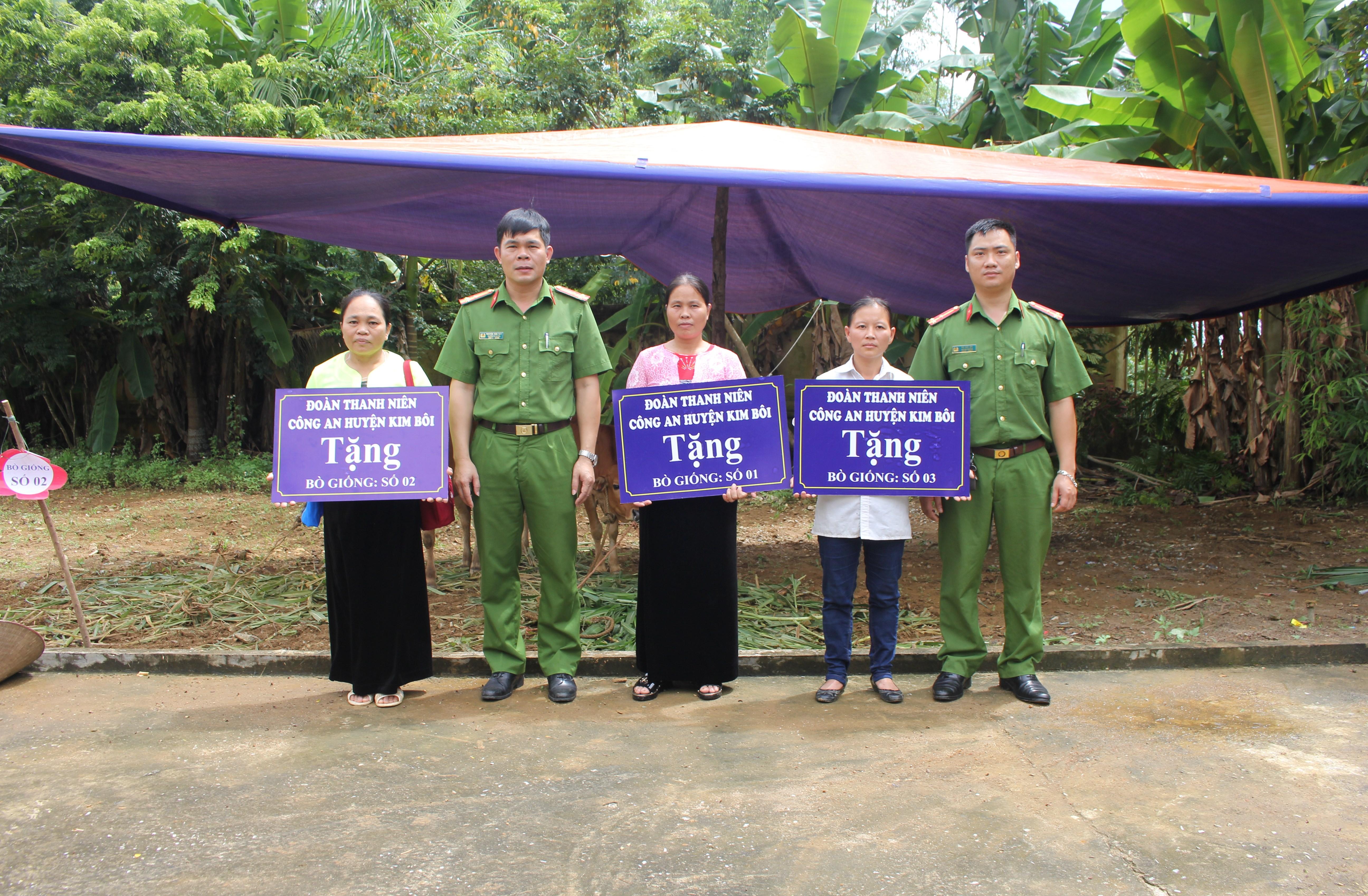 Thượng úy Bùi Đức Chí (ngoài cùng bên phải) trao tặng bò giống của Đoàn Thanh niên Công an huyện Kim Bôi cho các hộ đặc biệt khó khăn.