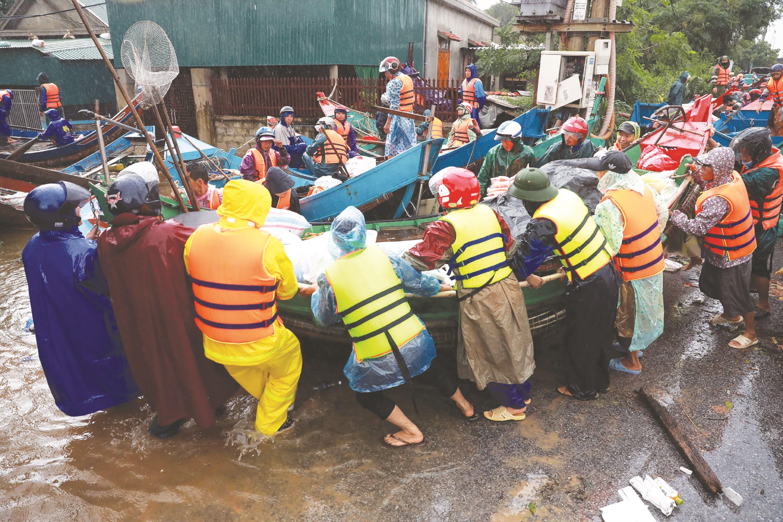 Những ngư dân ở vùng biển dùng ghe đánh cá đi vào vùng lũ để cứu người dân