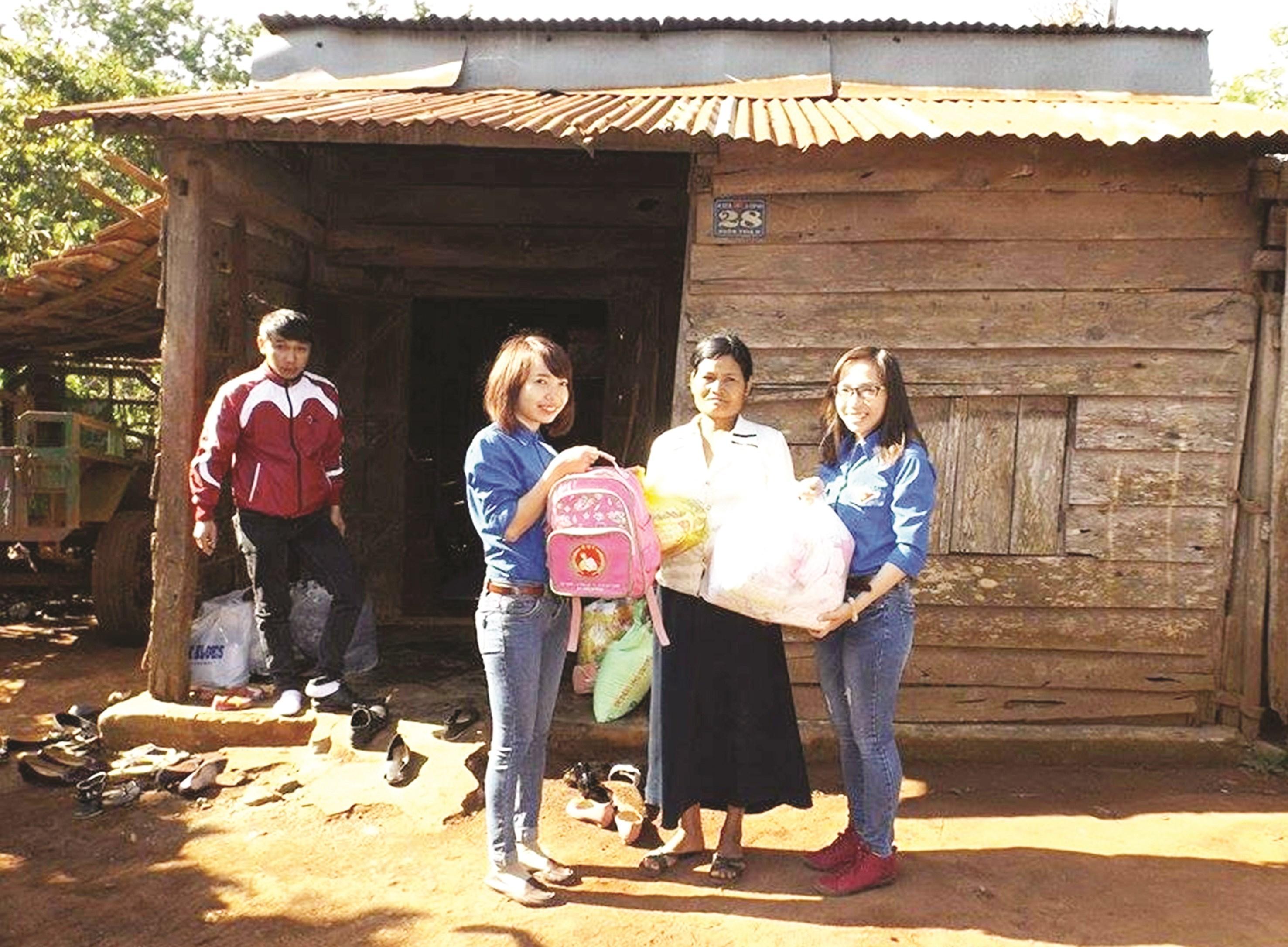 Cô Hương (bìa trái) trao quà cho bà con buôn làng