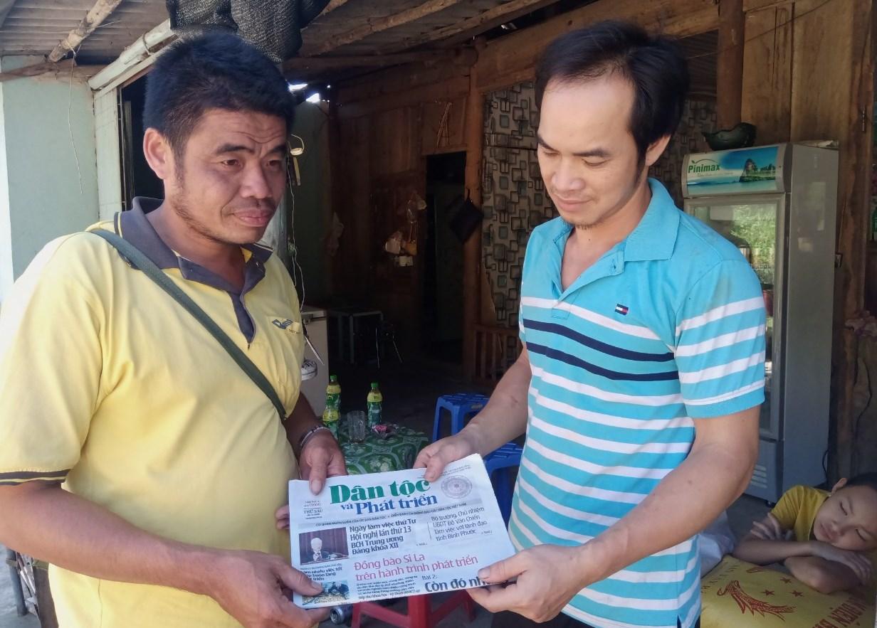 Bưu tá Ấu Văn Sơn (bên trái) phát Báo Dân tộc và Phát triển tới tận tay người dân
