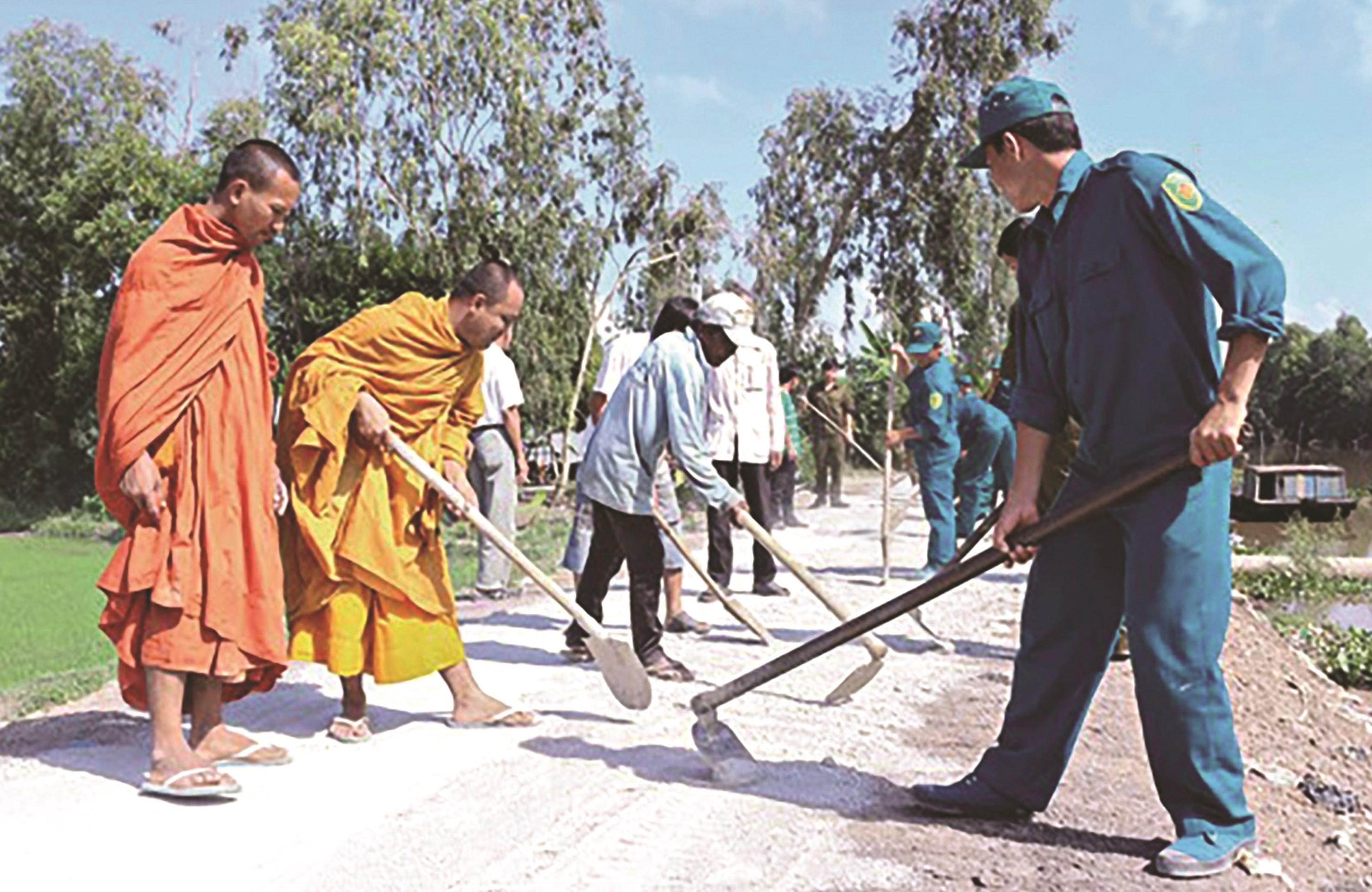 Người có uy tín trong cộng đồng dân tộc Khmer cùng người dân xây dựng đường giao thông nông thôn ở xã Cô Tô, huyện Tri Tôn (An Giang).