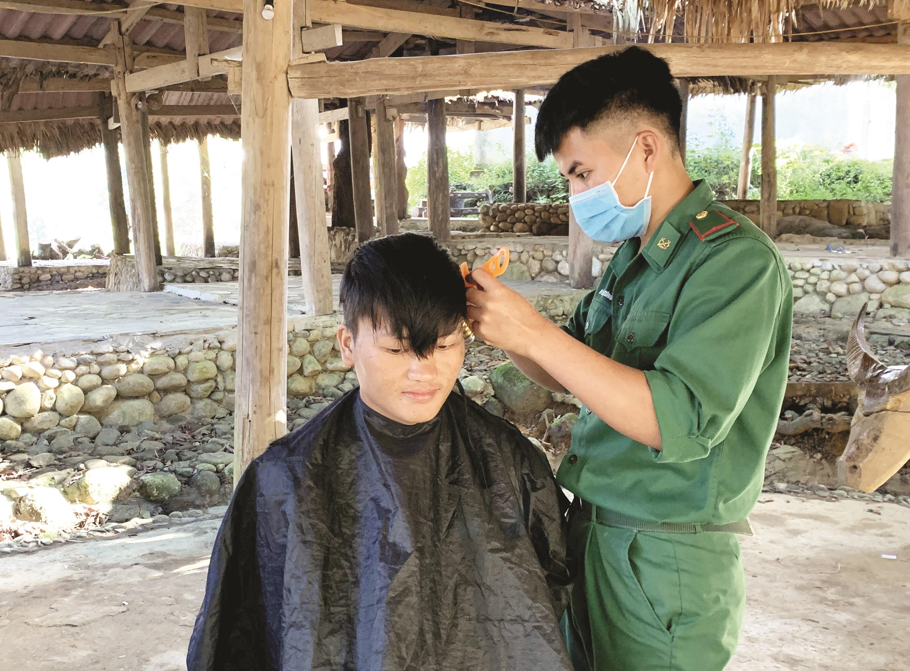 Tân binh Lò Văn Túng giúp người dân cắt tóc trong ngày sinh hoạt
