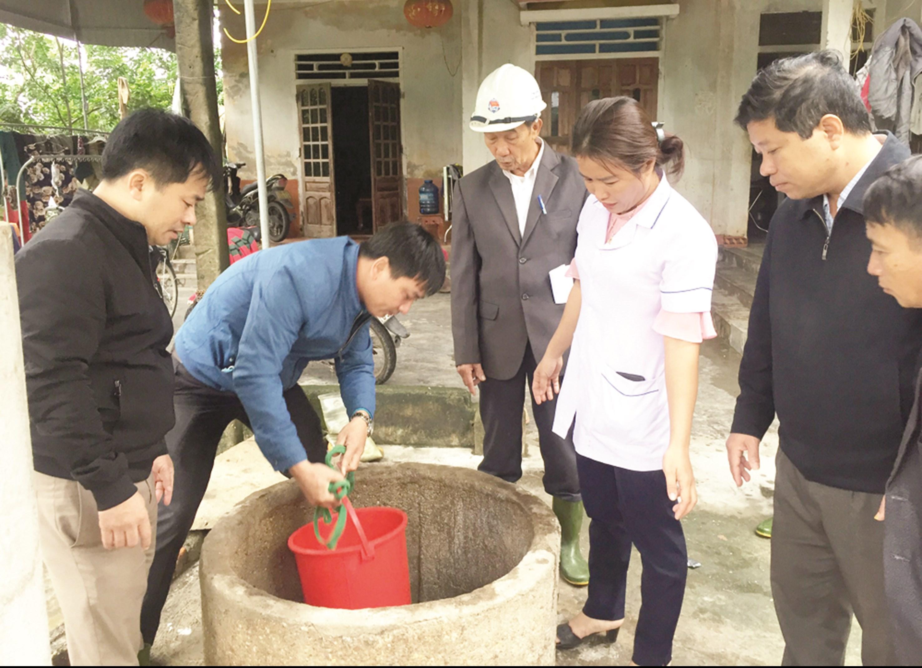 Nhân viên Trung tâm Kiểm soát dịch bệnh Hà Tĩnh hướng dẫn xử lý giếng nước bị ngập cho các hộ dân