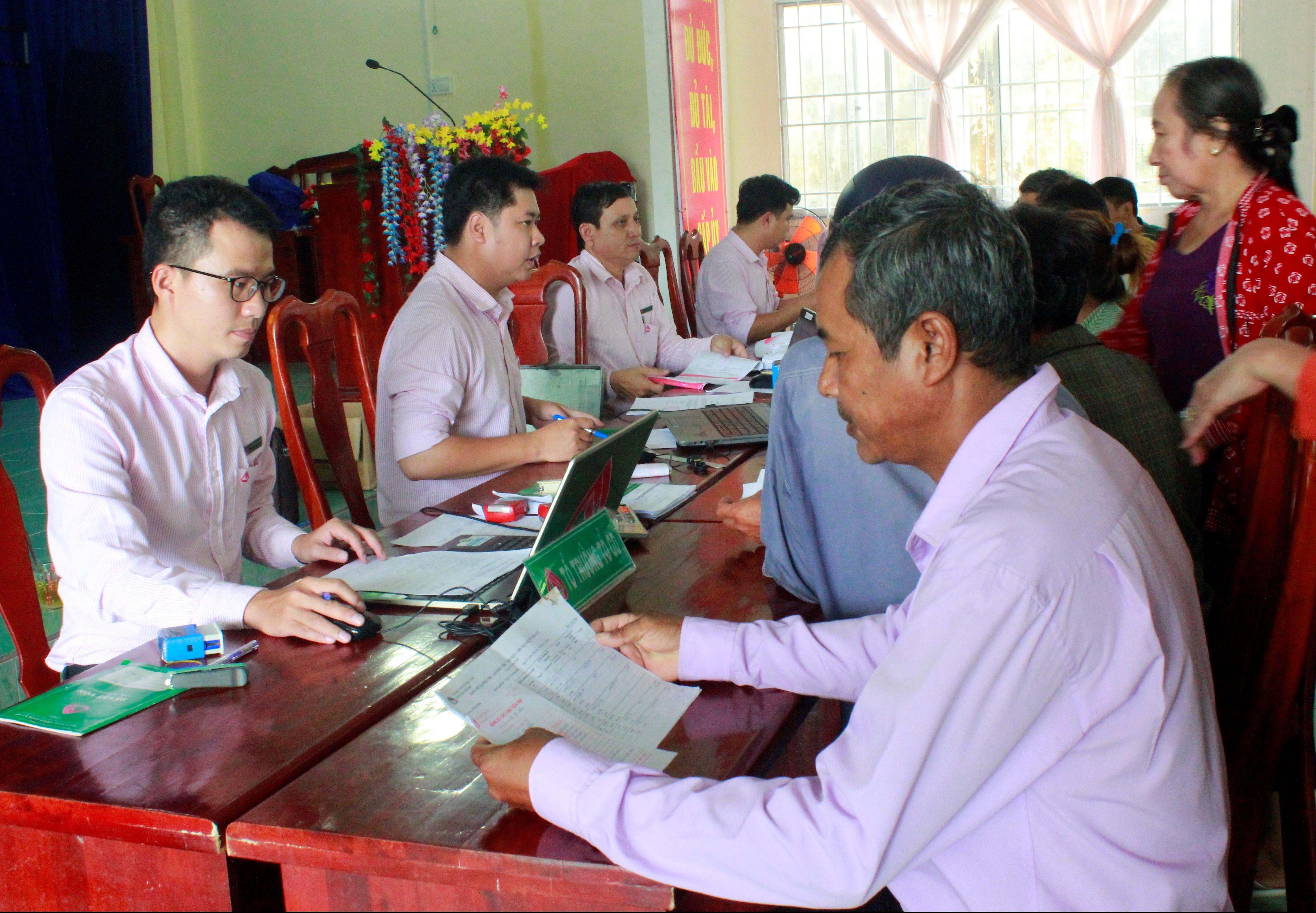 Cán bộ tín dụng NHCSXH huyện Thới Bình trao đổi với người vay vốn tại điểm giao dịch xã