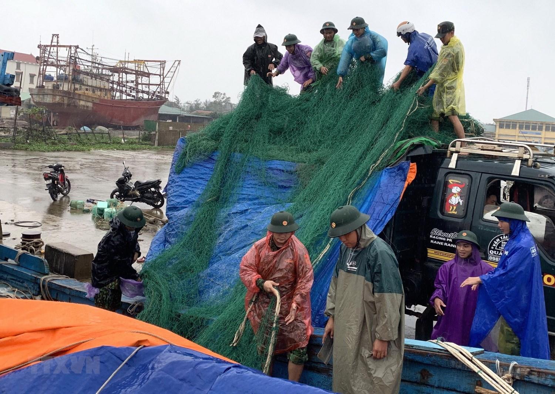 Bộ đội Biên phòng tỉnh Quảng Trị giúp ngư dân đưa lưới từ tàu cá lên bờ để phòng chống bão số 13.